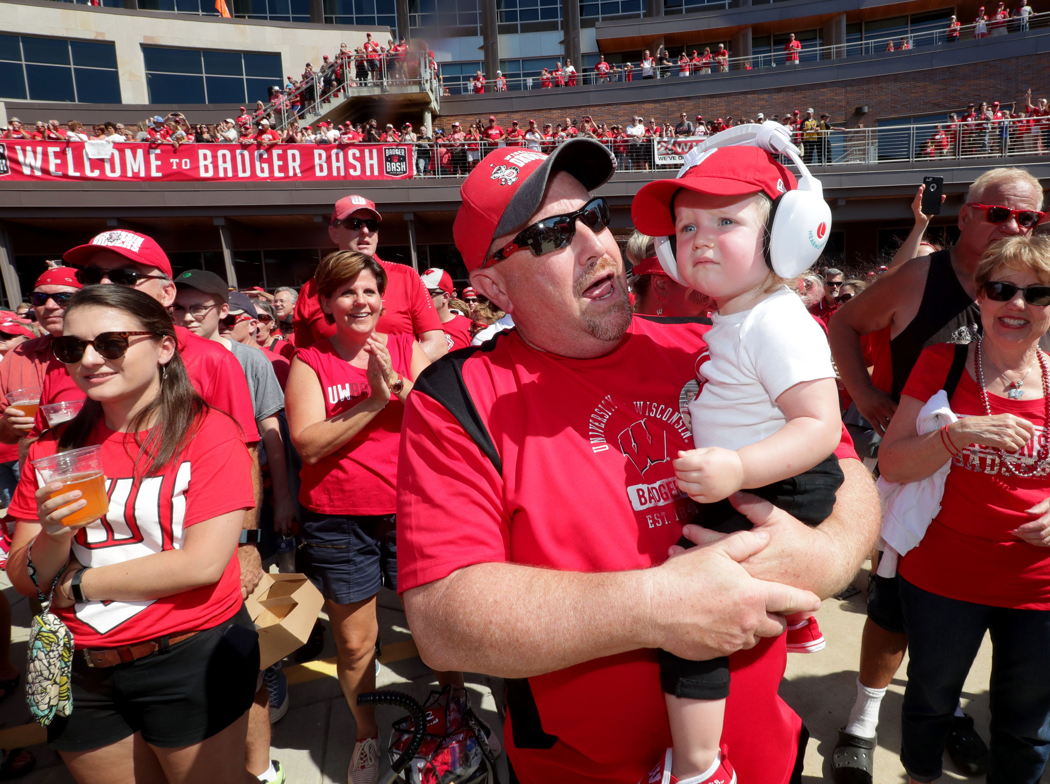Jack Pawley, of Menomonee Falls, holds his 1-year-old granddaughter Maisie Lennon, from Madison, as the UW alumni marching band performs at Union South before the Wisconsin-BYU game at Camp Randall Stadium.