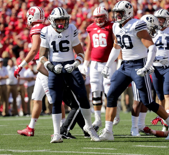 Brigham Young linebacker Sione Takitaki and defensive lineman Corbin Kaufusi celebrate a stop during the first half.