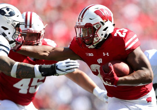 Wisconsin running back Jonathan Taylor stiff-arms Brigham Young linebacker Sione Takitaki.