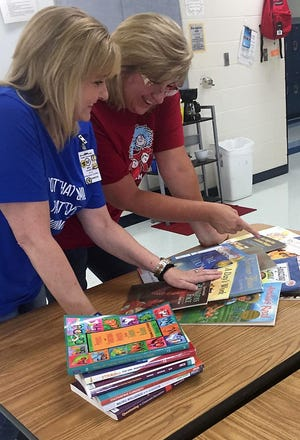 "Mountain Home Public School K-12 Dyslexia Coordinator Laurie Cramton (left) and Teachers on Special Assignment (TOSA) member Laura Strider look over some materials in preparation for Tuesday night's Family Engagement Night at Nelson-Wilks-Herron. ""Dinner and Literacy"" will provide resources to parents with students in K-sixth grade to increase literacy among younger elementary students."