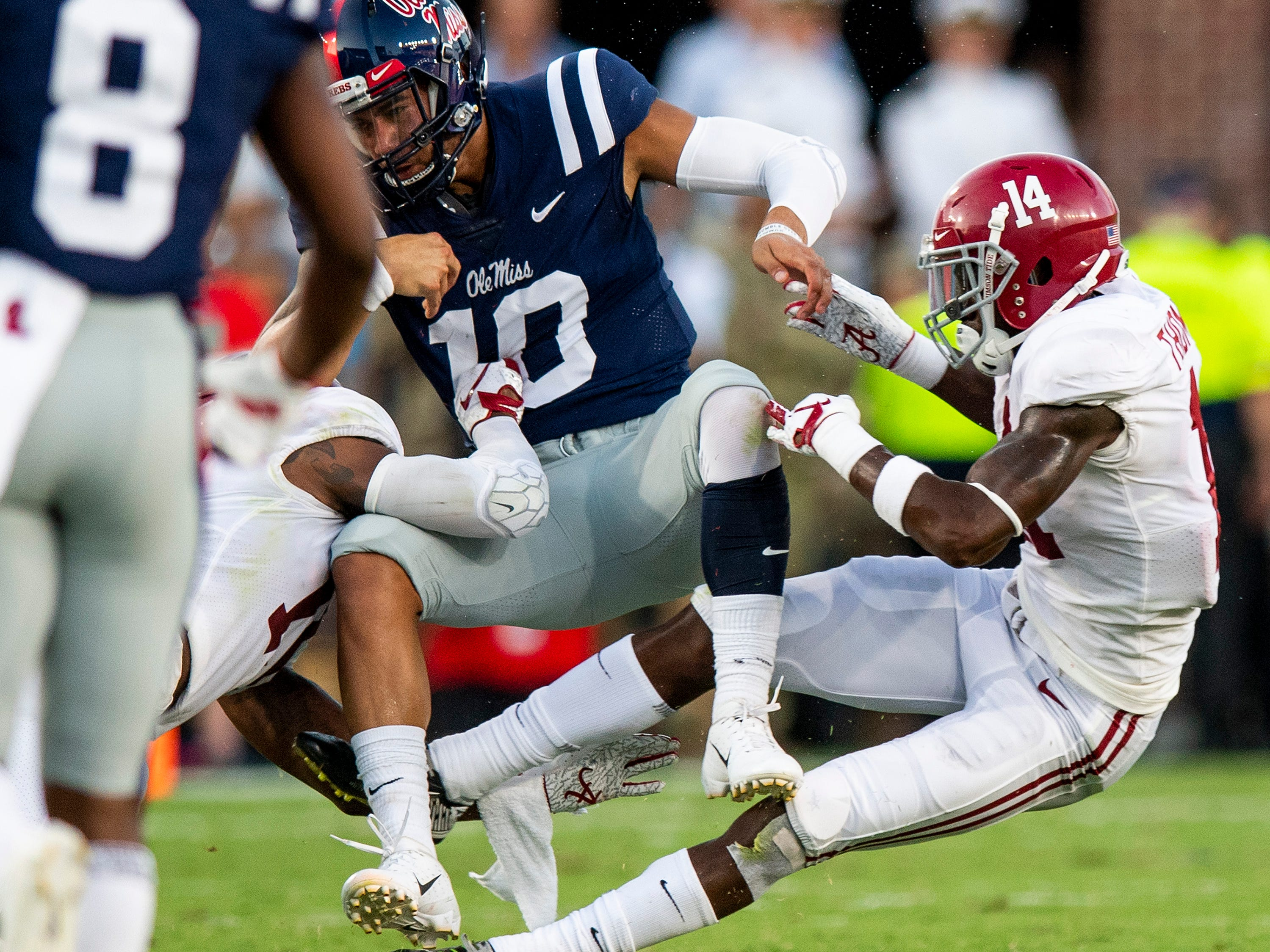 Alabama defensive back Deionte Thompson (14) and defensive back Xavier McKinney (15) tackle Ole Miss quarterback Jordan Ta'amu (10) causing a fumble In first half action in Oxford, Ms., on Saturday September 15, 2018.