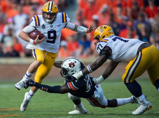 LSU's Joe Burrow (9) jumps over Auburn's Deshaun Davis (57) at Jordan-Hare Stadium in Auburn, Ala., on Saturday, Sept. 15, 2018. LSU defeated Auburn 22-21.