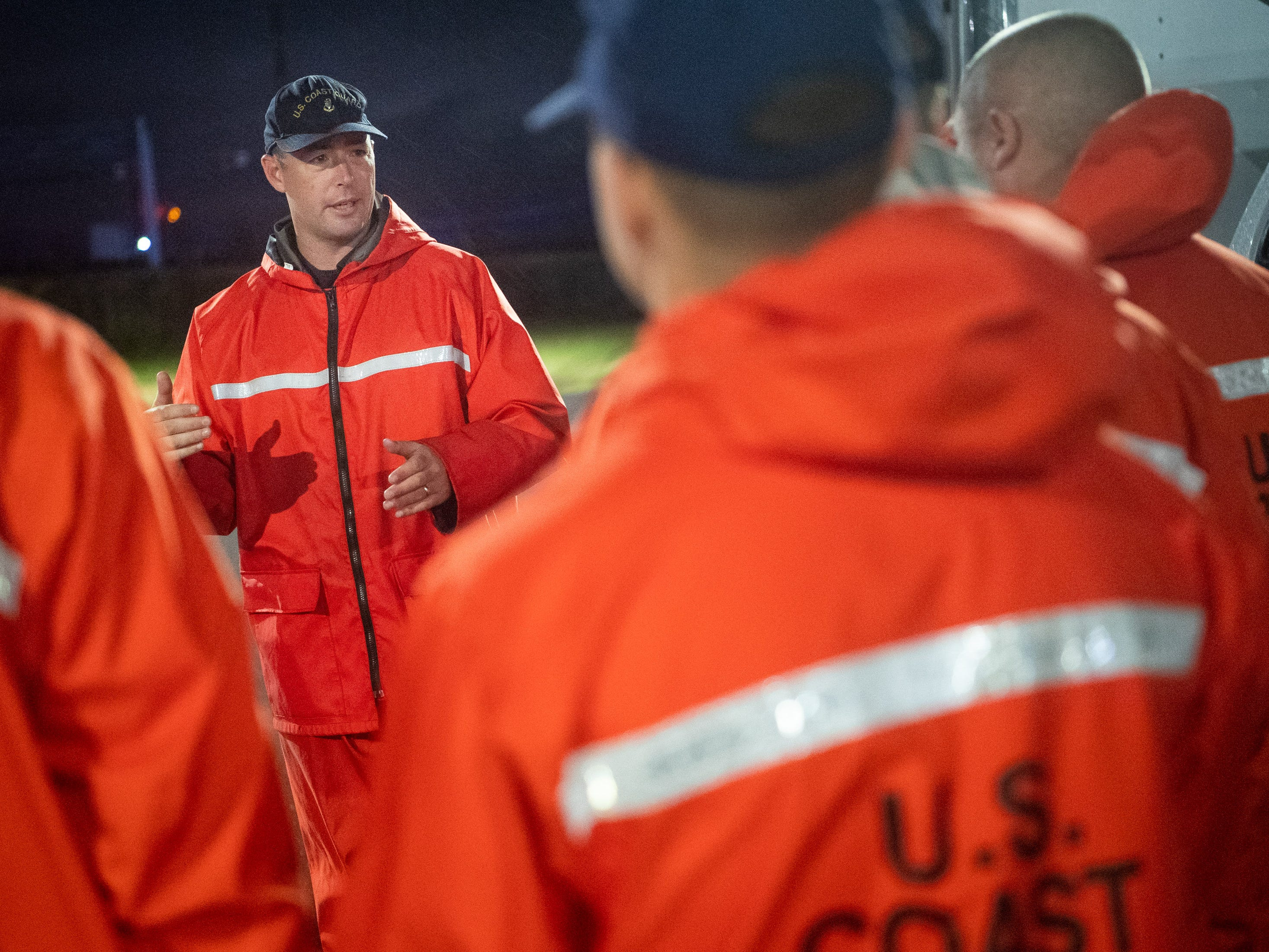 Coast Guard BMC Stephen Kelly, center, briefs his men before departing from their hotel in Lumberton, N.C., to conduct water rescues in Columbus County, Sunday, Sept. 16, 2018.