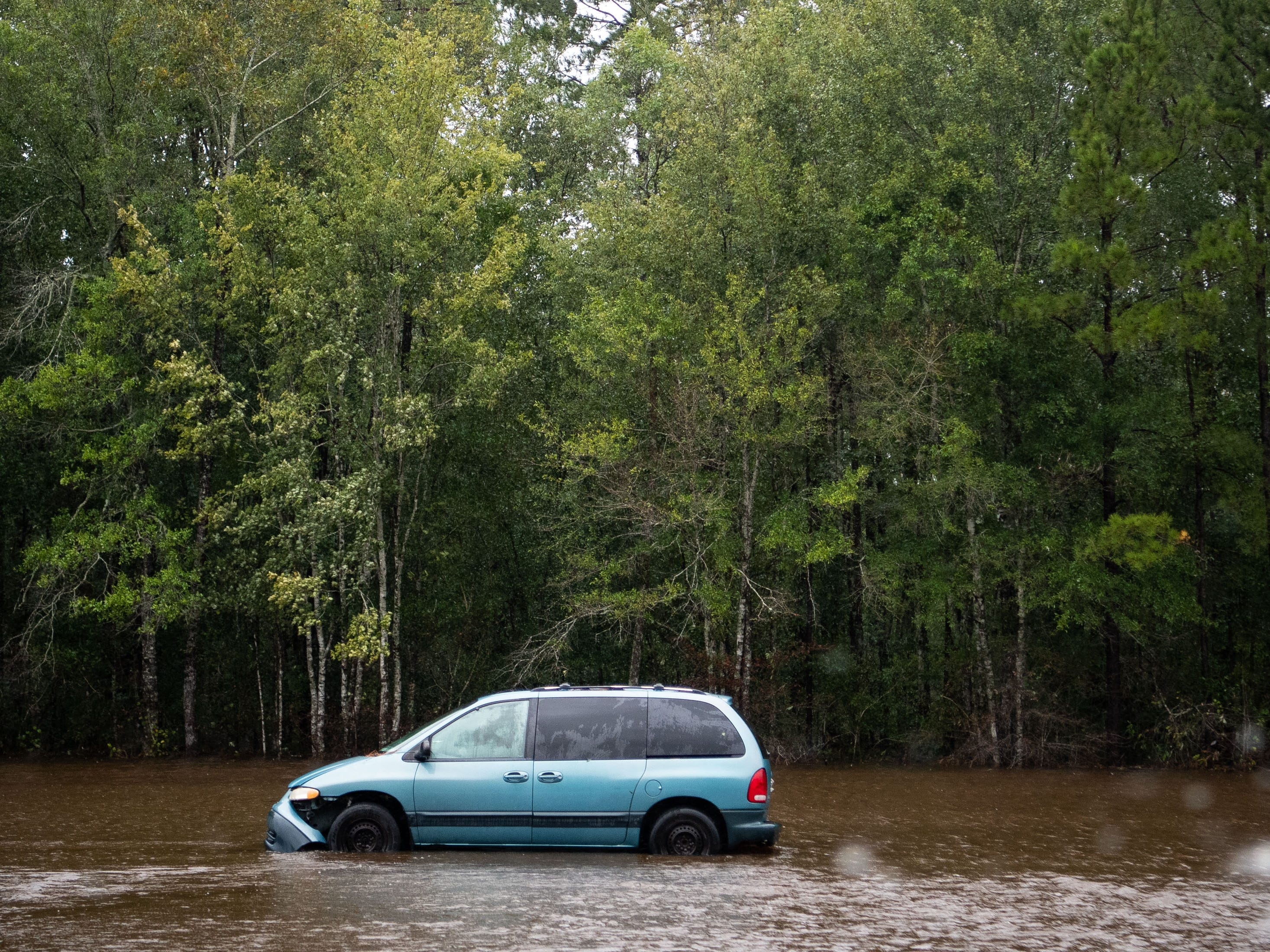 Abandoned cars in flood water on Andrew Jackson Highway near Hallsboro, N.C., Sunday, Sept. 16, 2018.