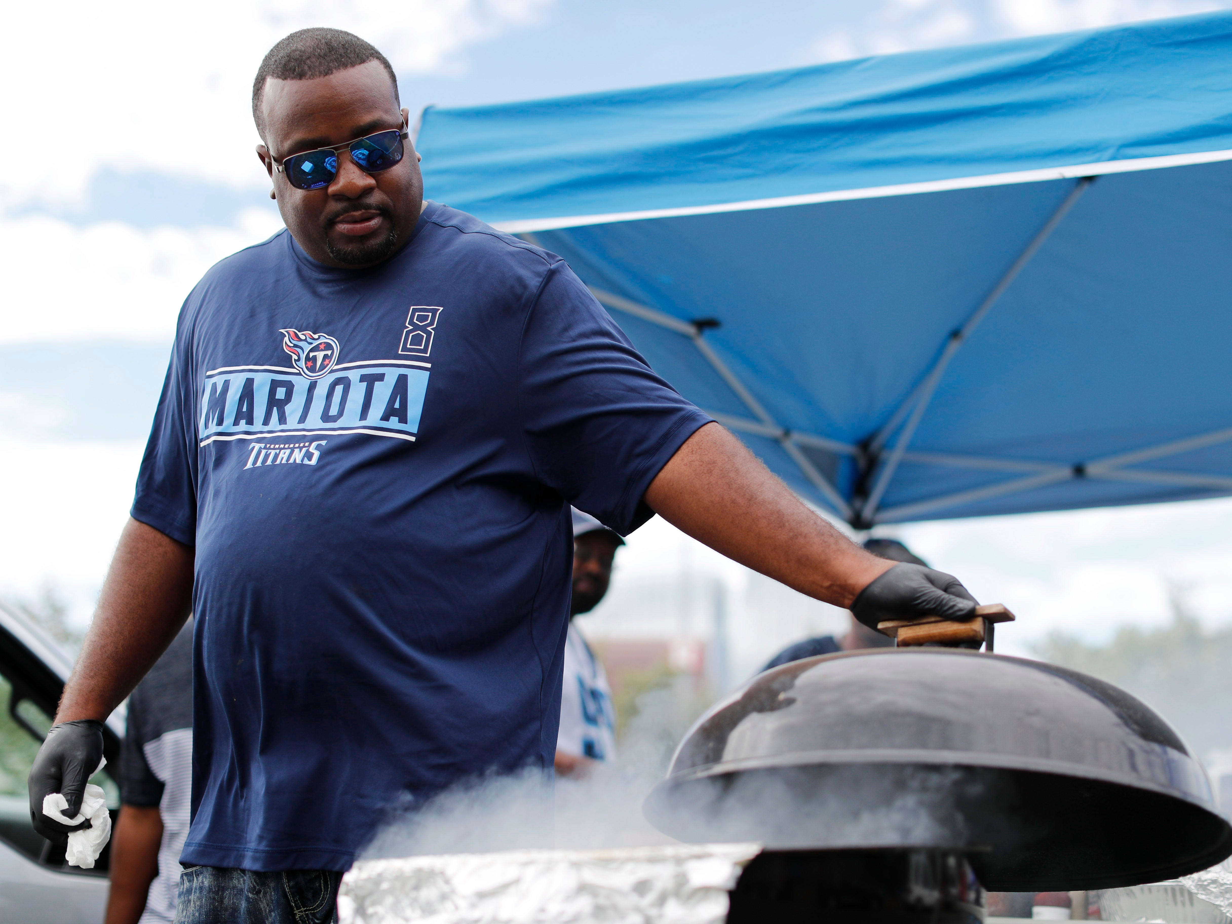 B.P. Poynter grills some burgers before the Titans' game against the Texans at Nissan Stadium Sunday, Sept. 16, 2018, in Nashville, Tenn.