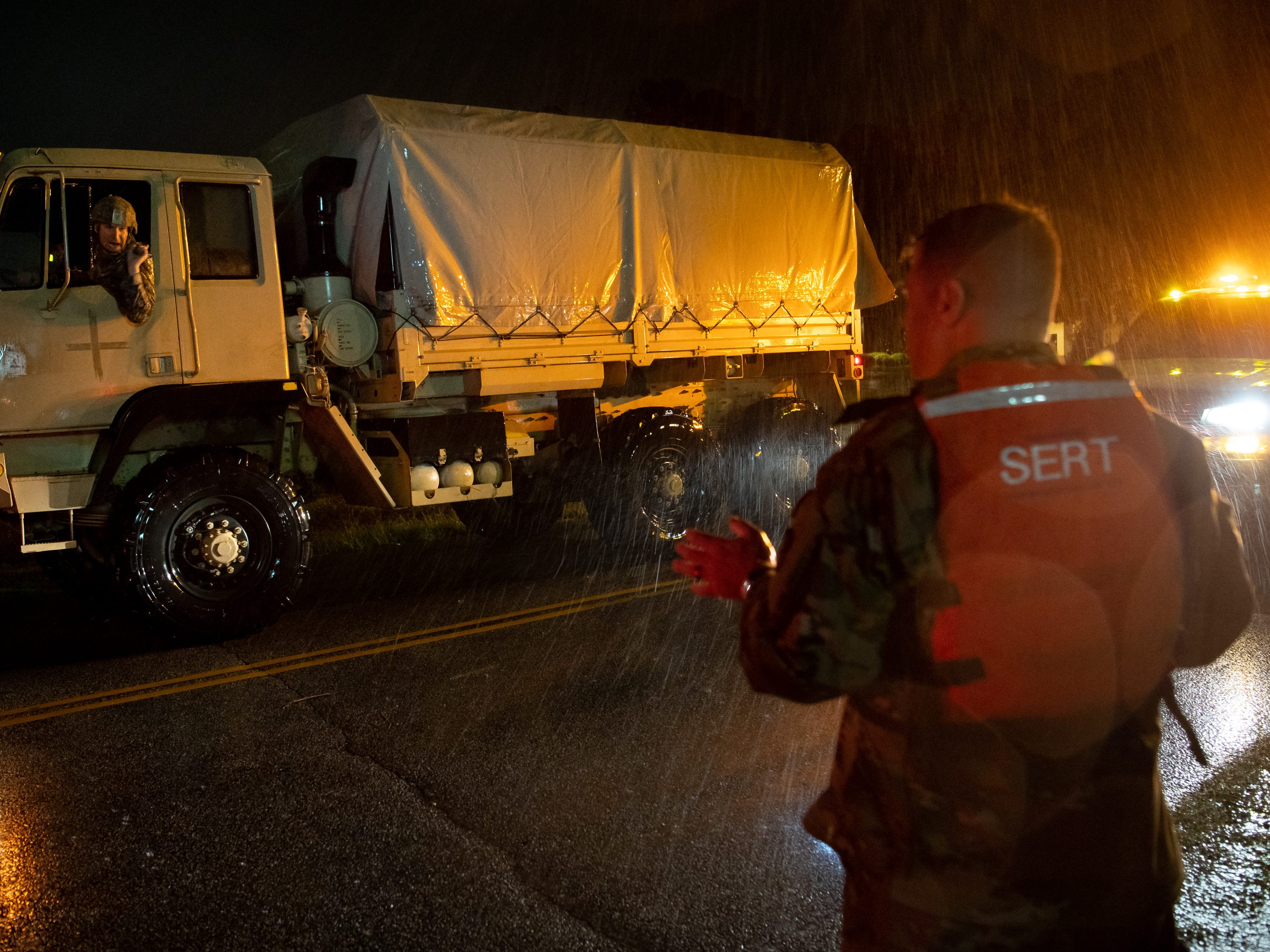 CSM Sid Baker, right, of the North Carolina National Guard, speaks with the driver of a National Guard truck carrying evacuees from a flooded neighborhood as rain from Tropical Storm Florence continues to fall on Lumberton, N.C., Saturday, Sept. 15, 2018.