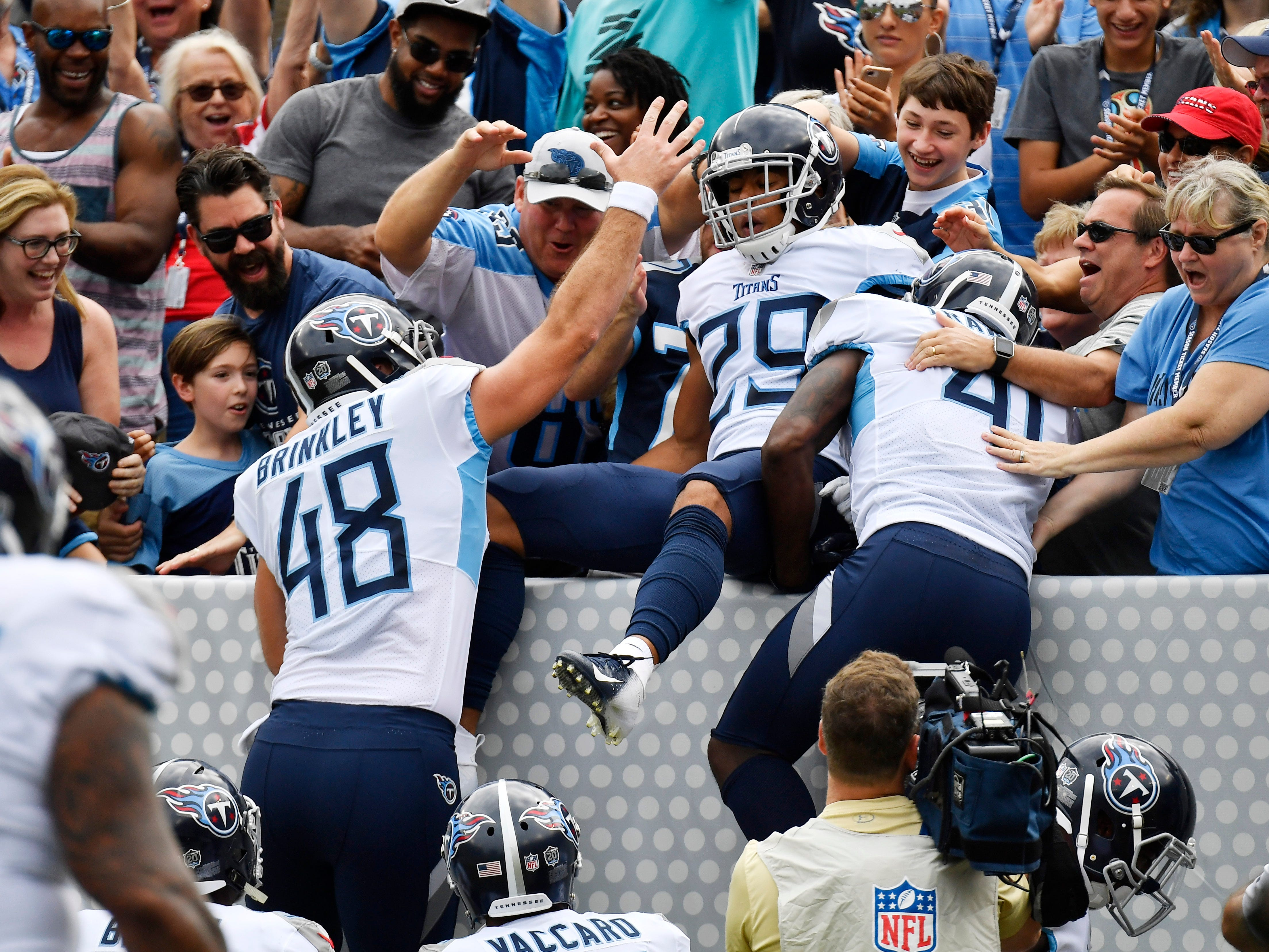 Titans cornerback Dane Cruikshank (29) celebrates his touchdown with long snapper Beau Brinkley (48), safety Brynden Trawick (41) and the fans at Nissan Stadium Sunday, Sept. 16, 2018, in Nashville, Tenn.