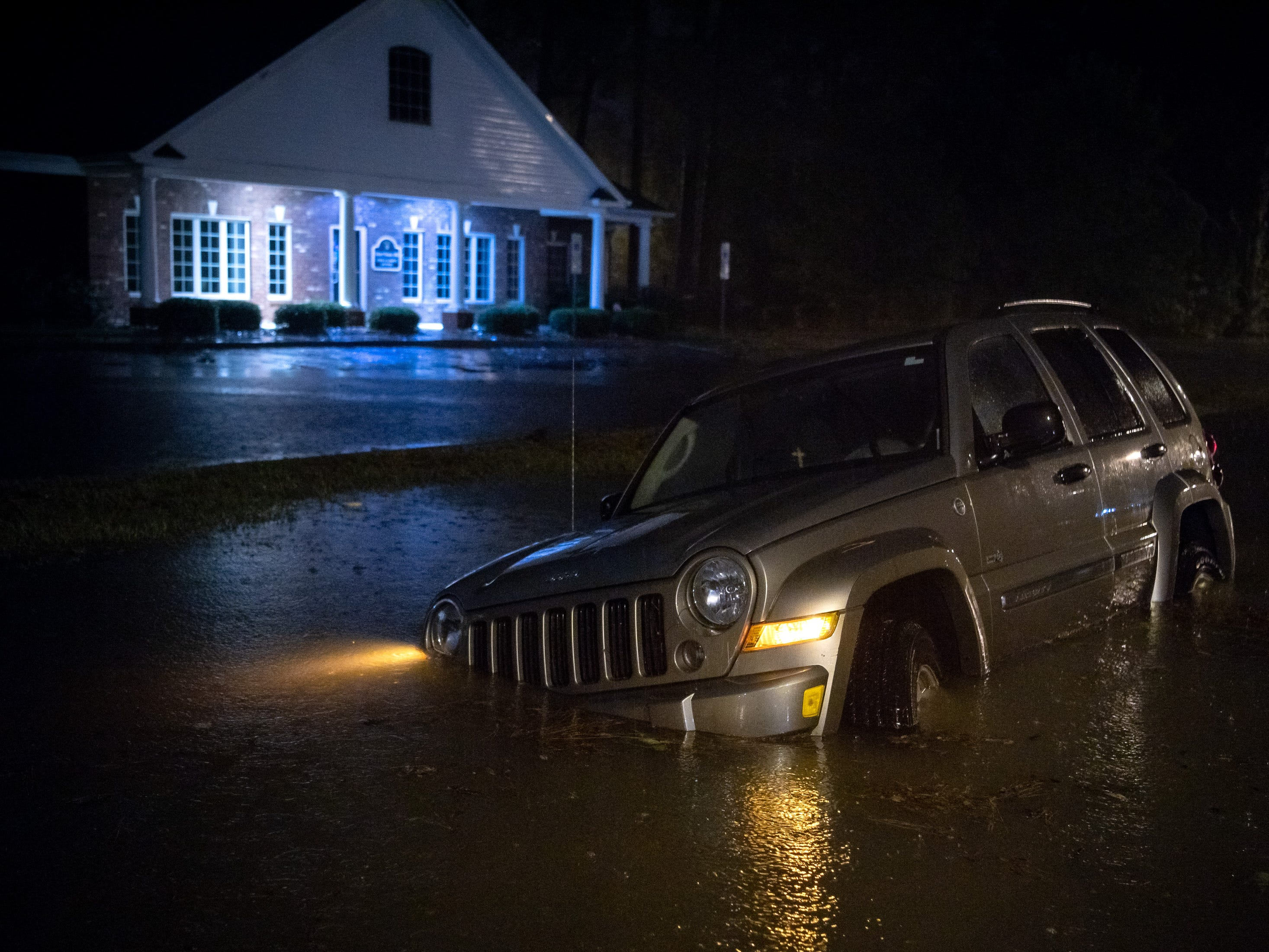 An abandoned SUV sits in a flooded neighborhood as rain from Tropical Storm Florence continues to fall on Lumberton, N.C., Saturday, Sept. 15, 2018.