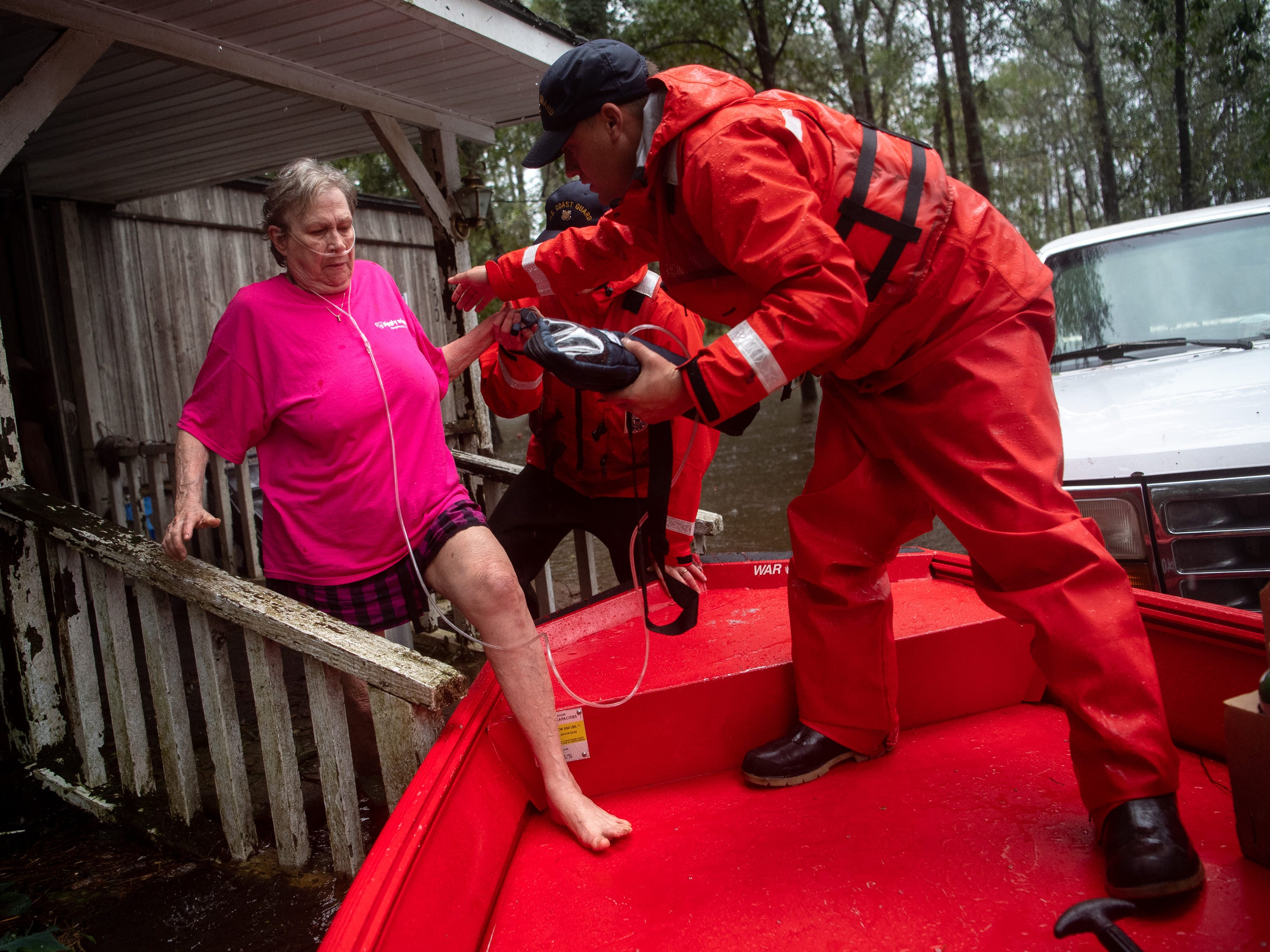 Coast Guard ME2 Blake Gwinn helps Josephine Horne, left, evacuate from her flooded home in Columbus County, N.C., Sunday, Sept. 16, 2018.