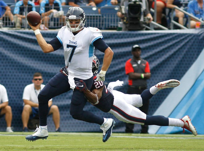 Texans safety Justin Reid (20) hangs onto Titans quarterback Blaine Gabbert (7) as he looks to throw in the second quarter Sunday.