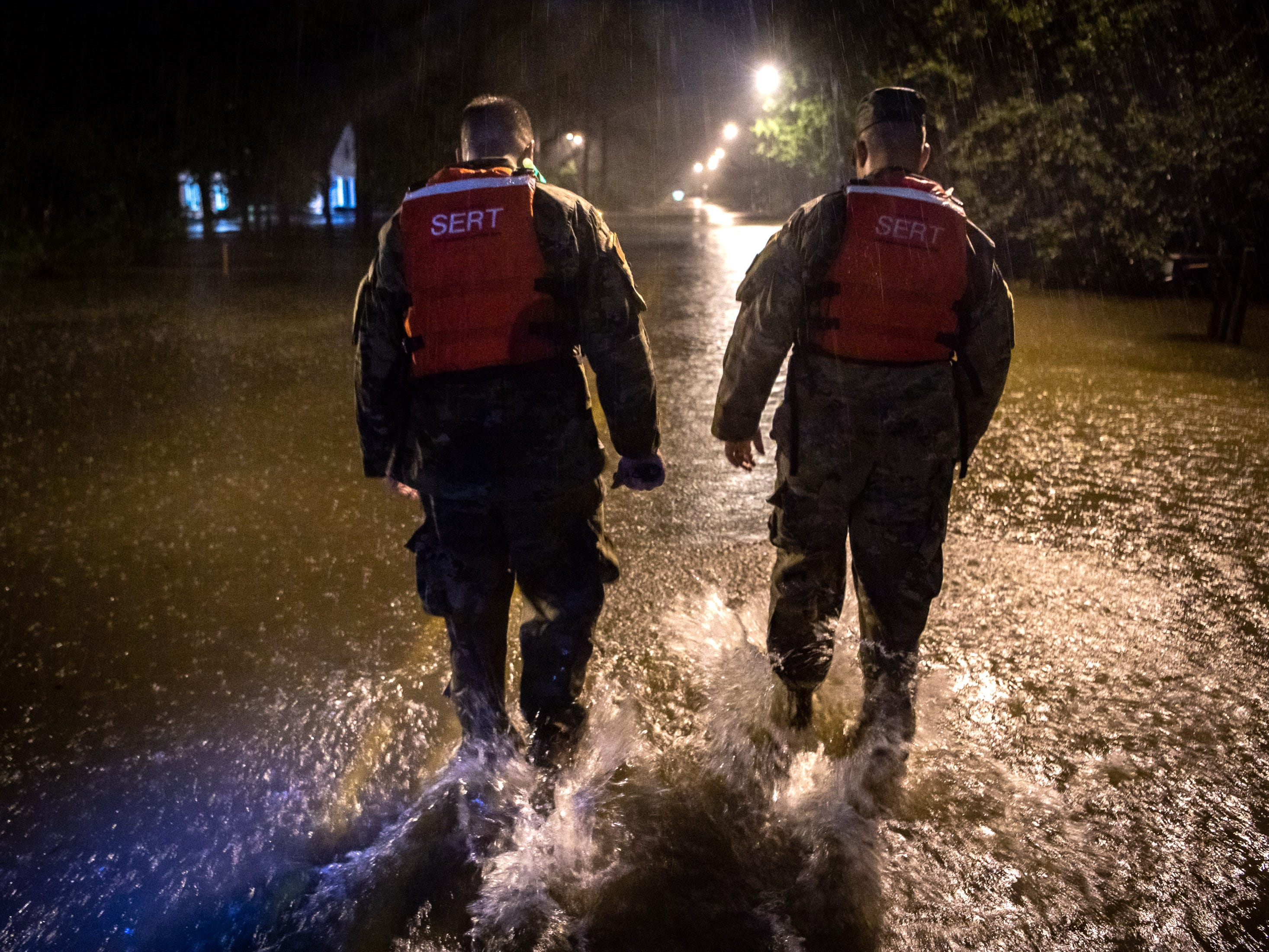 CSM Sid Baker, left, and 1SG Christopher Jones, right, of the North Carolina National Guard patrol a flooded neighborhood as rain from Tropical Storm Florence continues to fall on Lumberton, N.C., Saturday, Sept. 15, 2018.