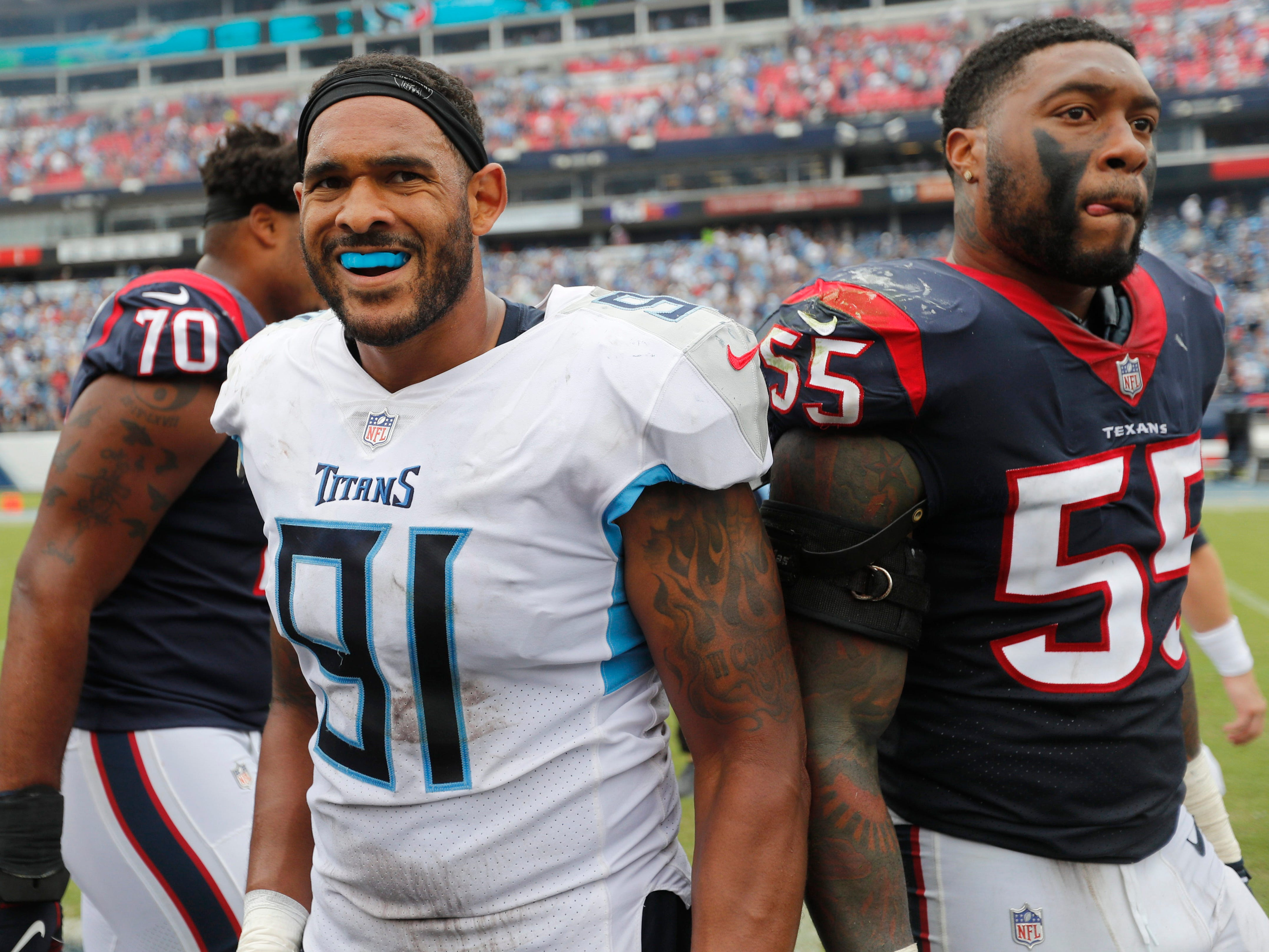 Titans linebacker Derrick Morgan (91) and Texans linebacker Benardrick McKinney (55) react after the Titans' win at Nissan Stadium Sunday, Sept. 16, 2018, in Nashville, Tenn.