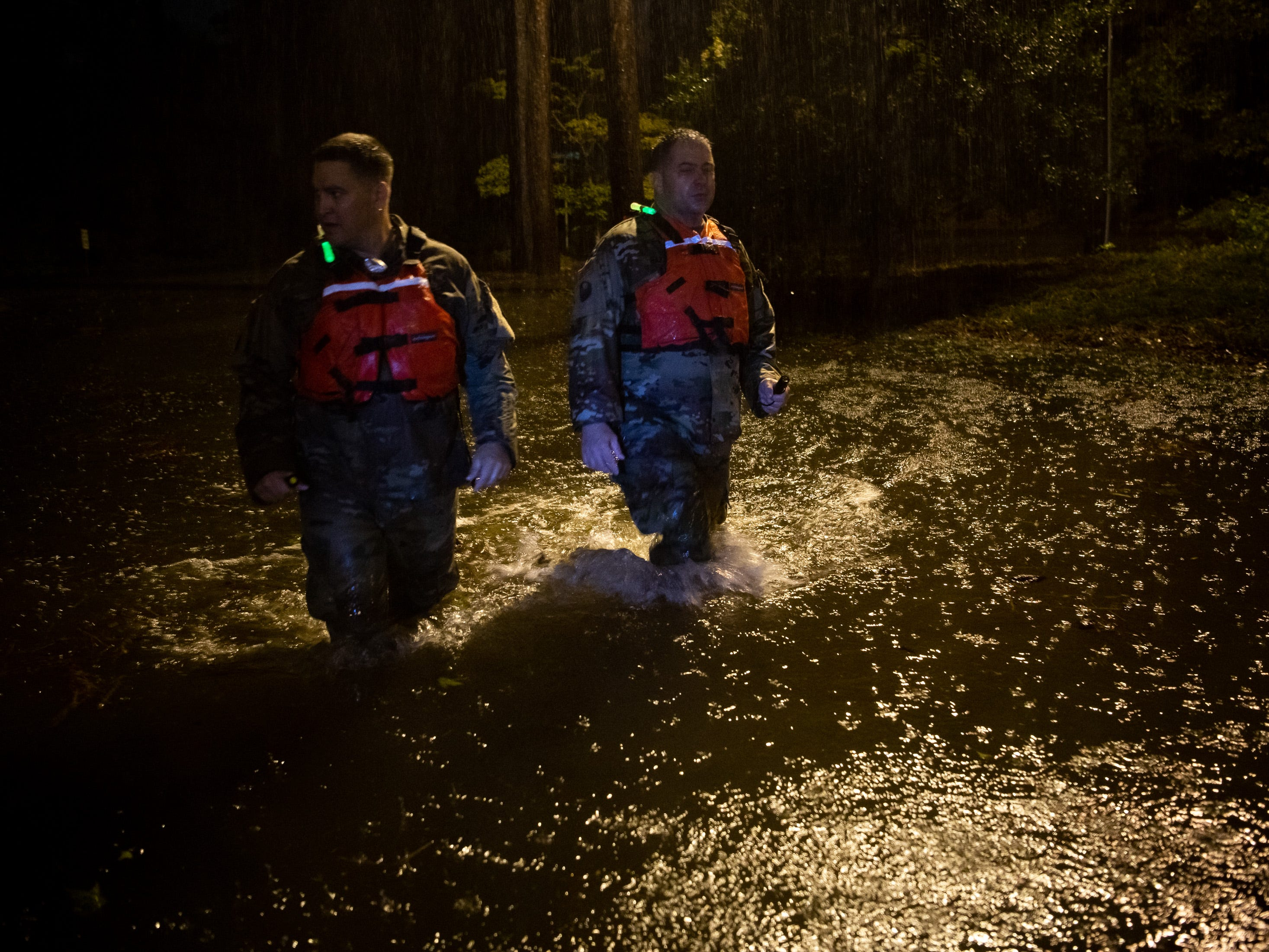 1SG Christopher Jones, left, and CSM Sid Baker, right, of the North Carolina National Guard patrol a flooded neighborhood as rain from Tropical Storm Florence continues to fall on Lumberton, N.C., Saturday, Sept. 15, 2018.
