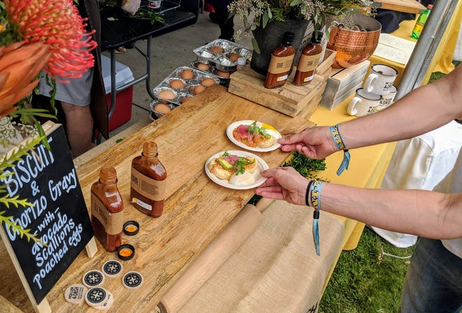 Quick hands grab biscuits and chorizo gravy from Holler & Dash, choosing to forgo a dash of their homemade hot sauce, at the Music City Food + Wine Festival.