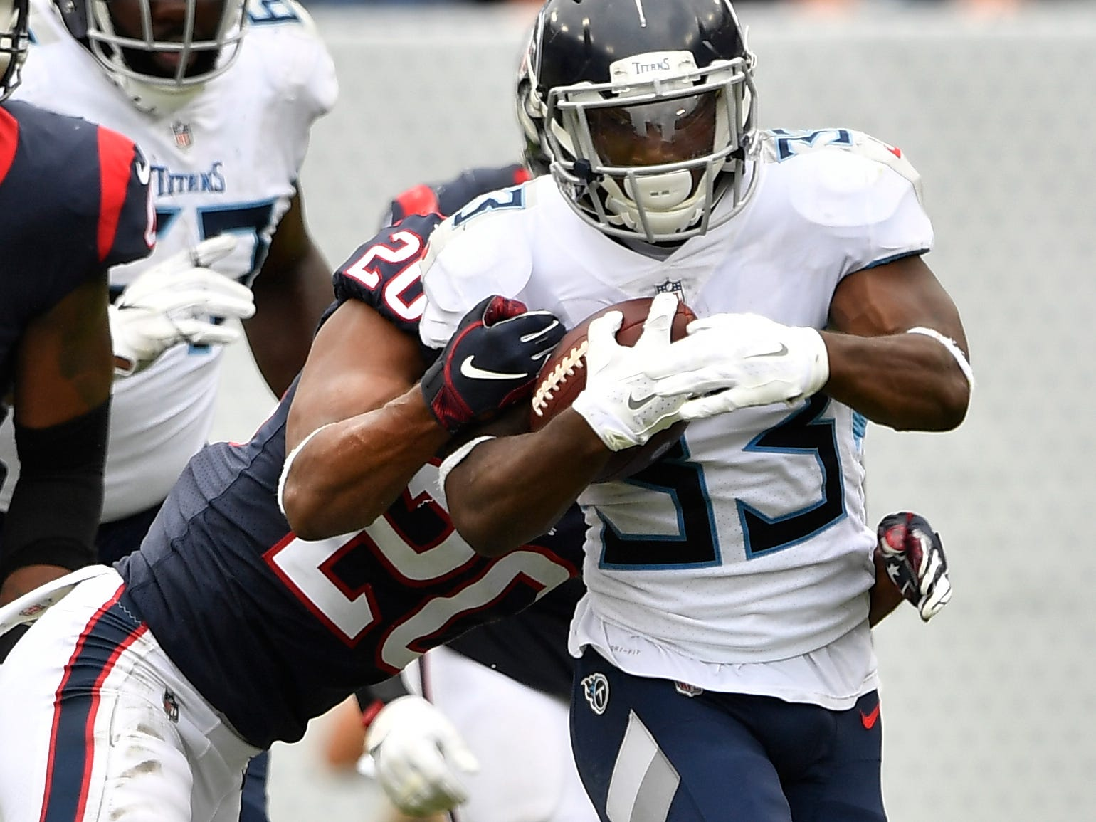 Titans running back Dion Lewis (33) gets wrapped up by Texans safety Justin Reid (20) and cornerback Johnson Bademosi (23) in the second half at Nissan Stadium Sunday, Sept. 16, 2018, in Nashville, Tenn.