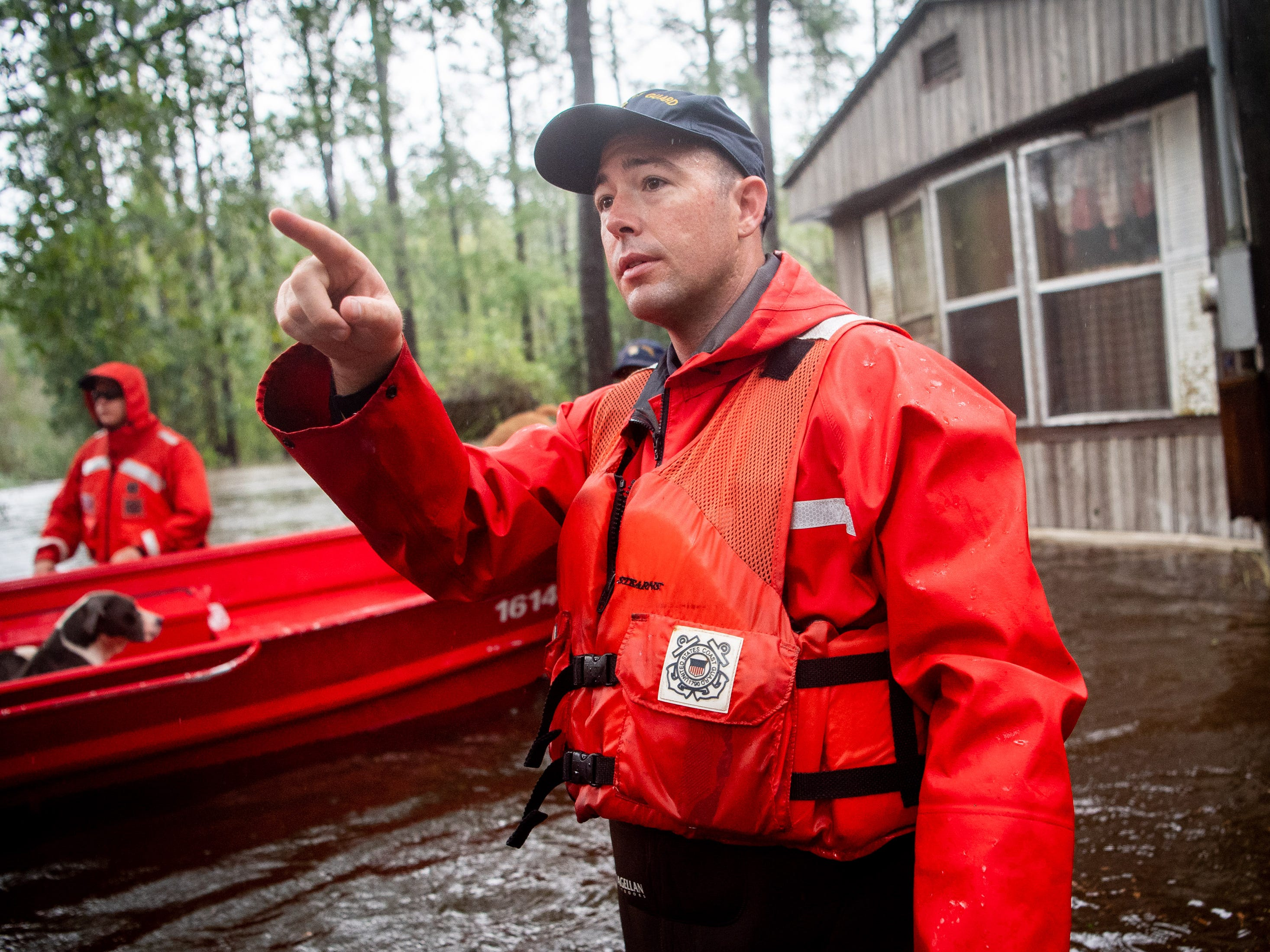 Coast Guard BMC Stephen Kelly directs his men through a flooded neighborhood in Columbus County, N.C., Sunday, Sept. 16, 2018.