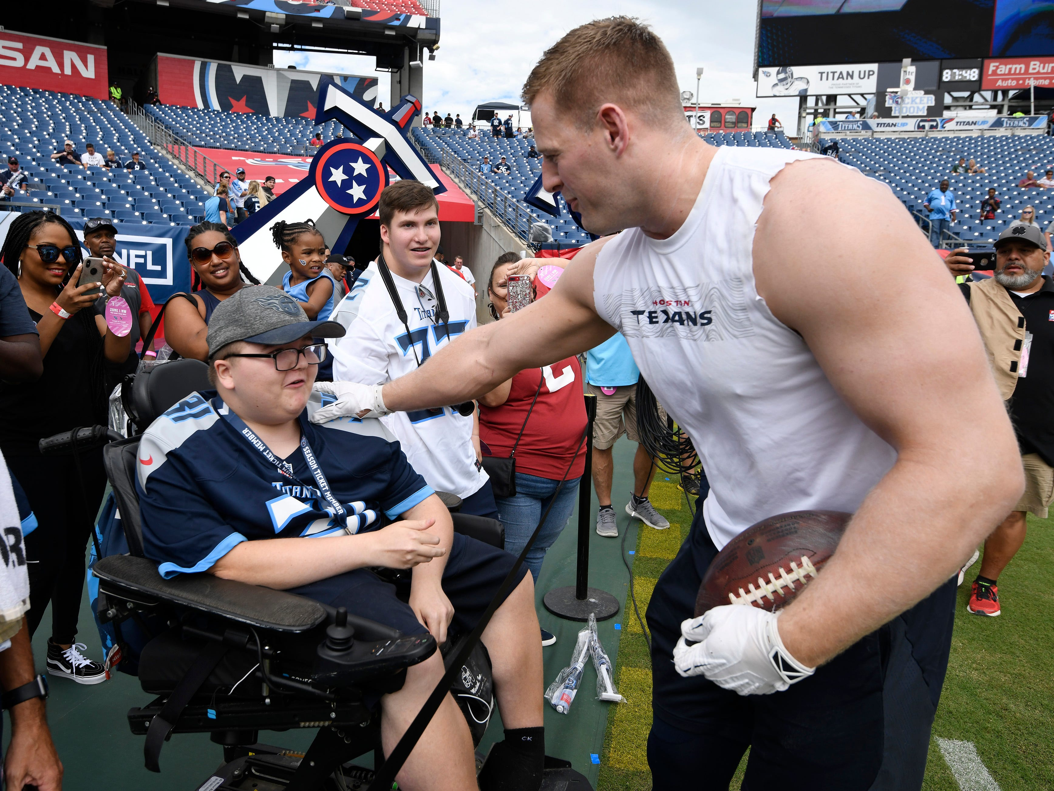 Texans defensive end J.J. Watt (99) greets Cameron Parker before the game at Nissan Stadium Sunday, Sept. 16, 2018, in Nashville, Tenn.