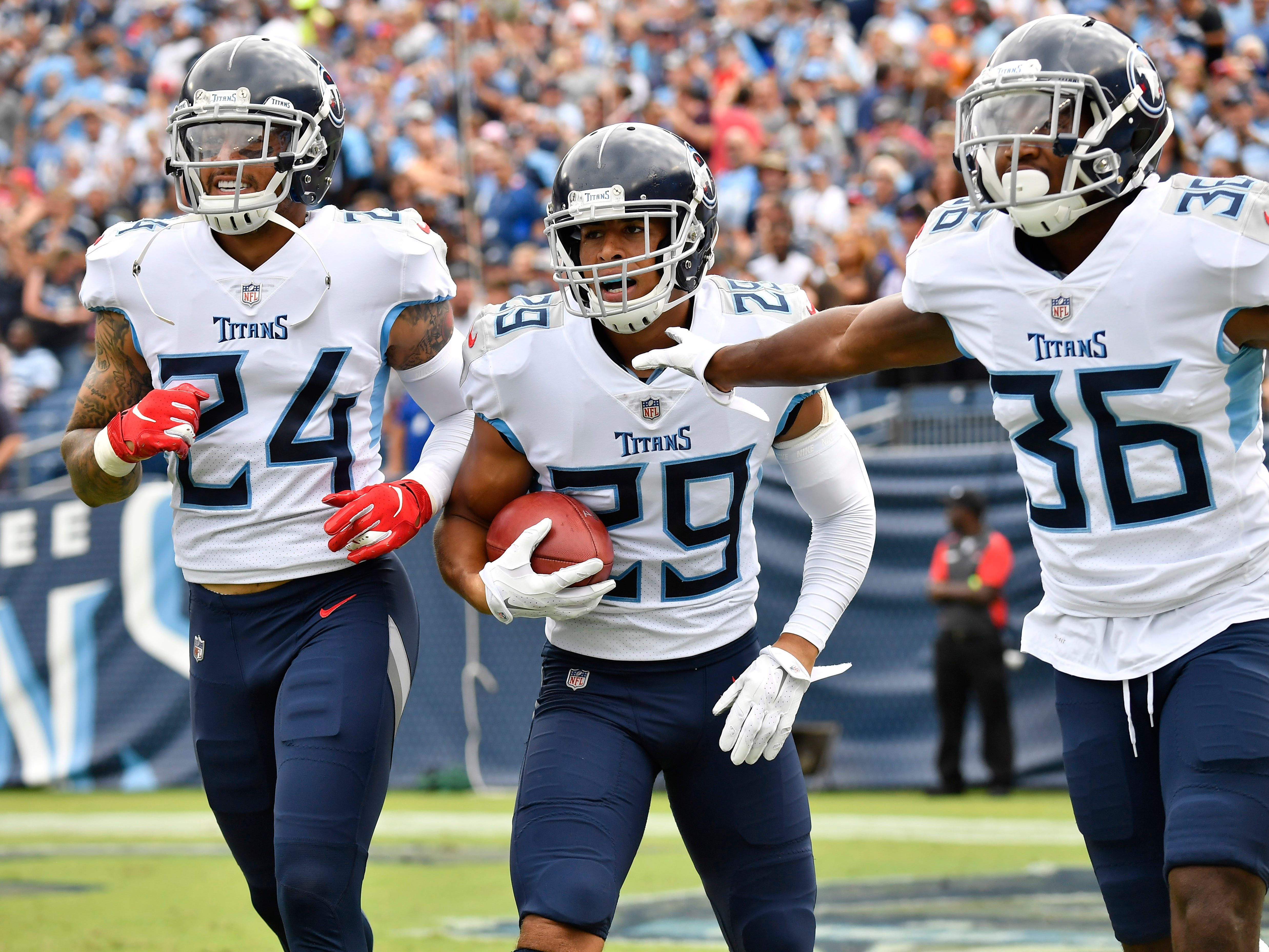 Titans cornerback Dane Cruikshank (29) celebrates his touchdown with safety Kenny Vaccaro (24) and cornerback LeShaun Sims (36) in the first quarter at Nissan Stadium Sunday, Sept. 16, 2018, in Nashville, Tenn.