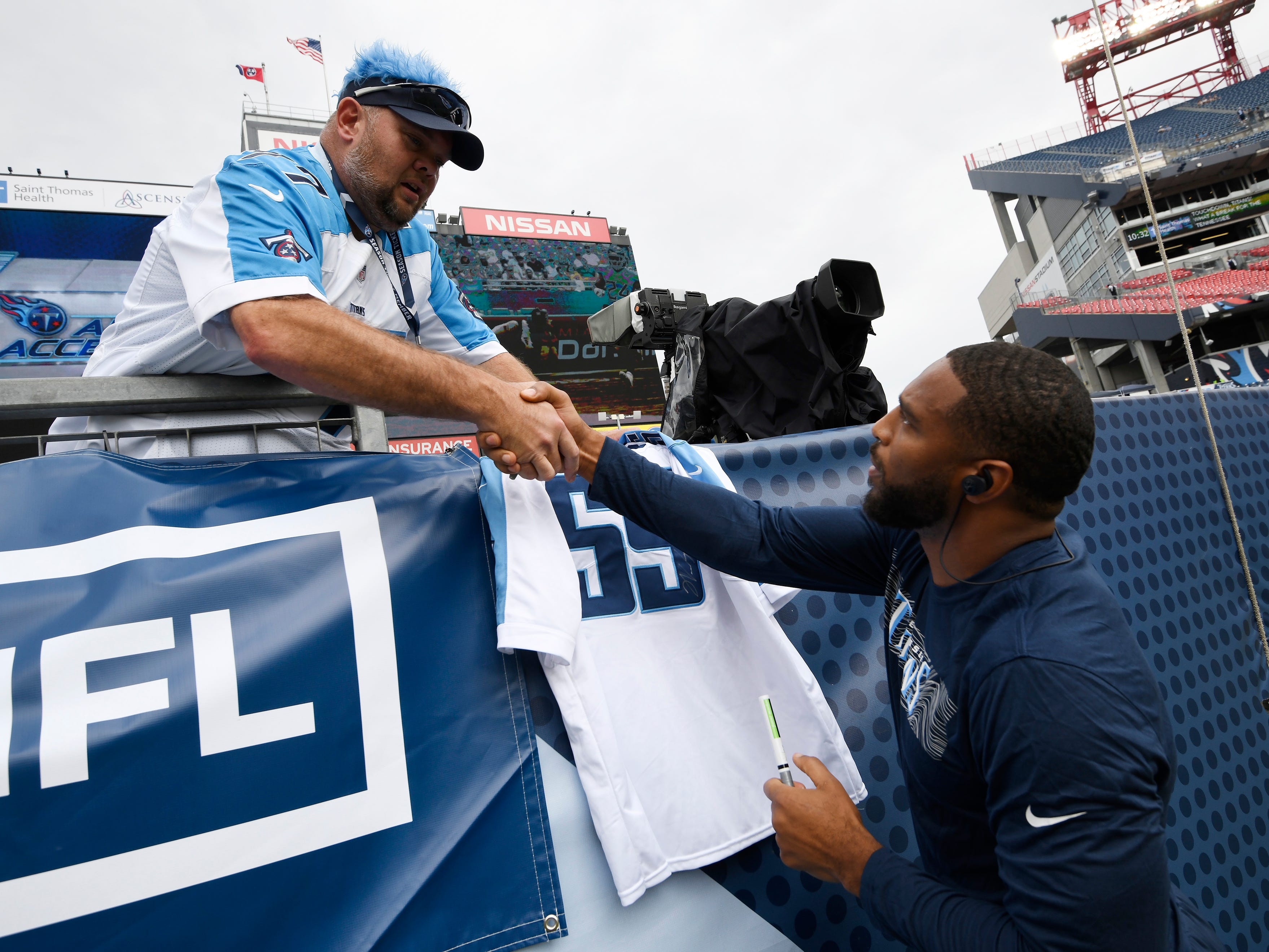 Titans linebacker Wesley Woodyard (59) shakes hands with a fan before the game against the Texans at Nissan Stadium Sunday, Sept. 16, 2018, in Nashville, Tenn.