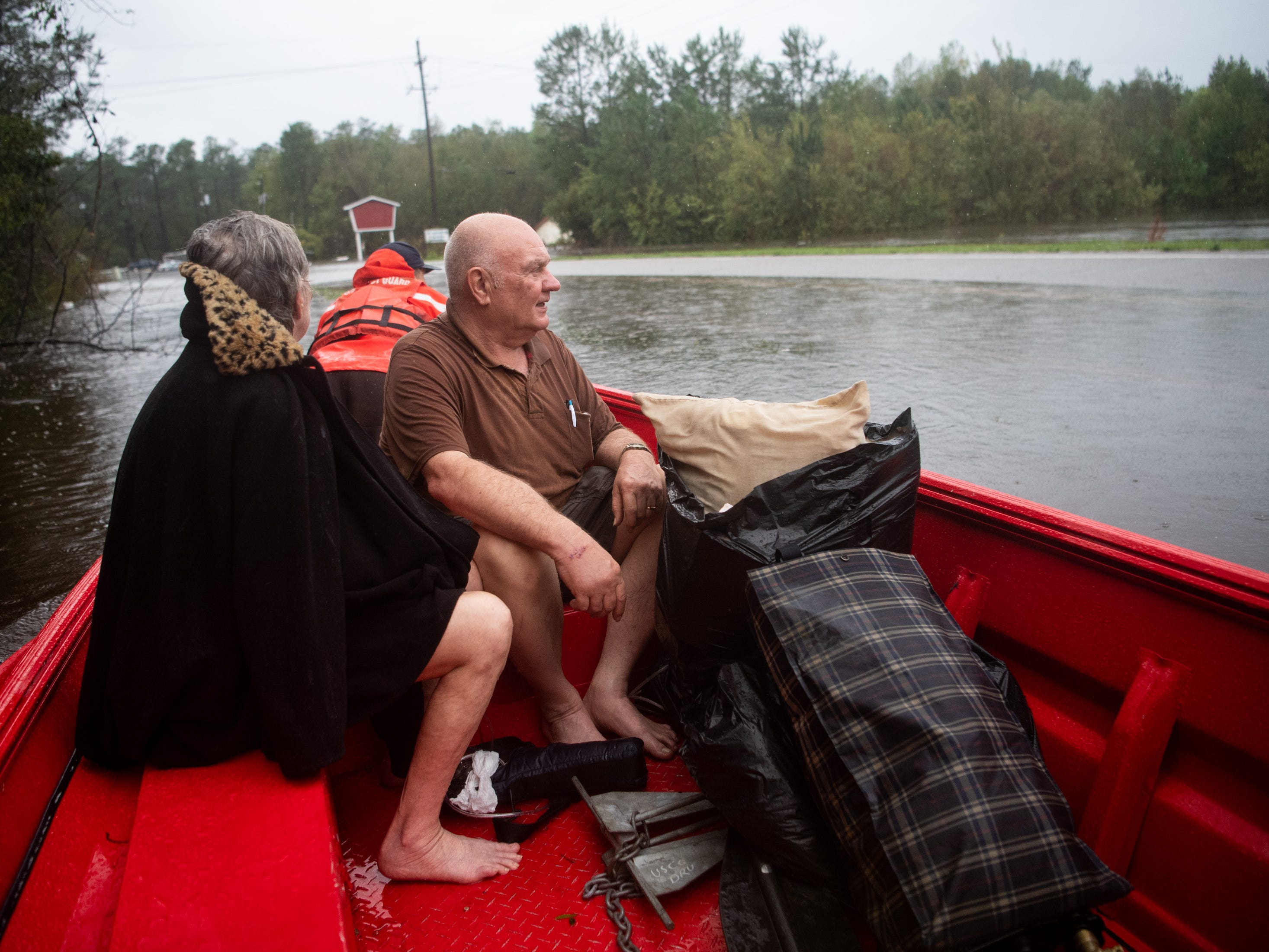 Josephine Horne, left, and Jackie Horne, center are evacuated from their flooded home in Columbus County, N.C., by Coast Guardsmen, Sunday, Sept. 16, 2018.