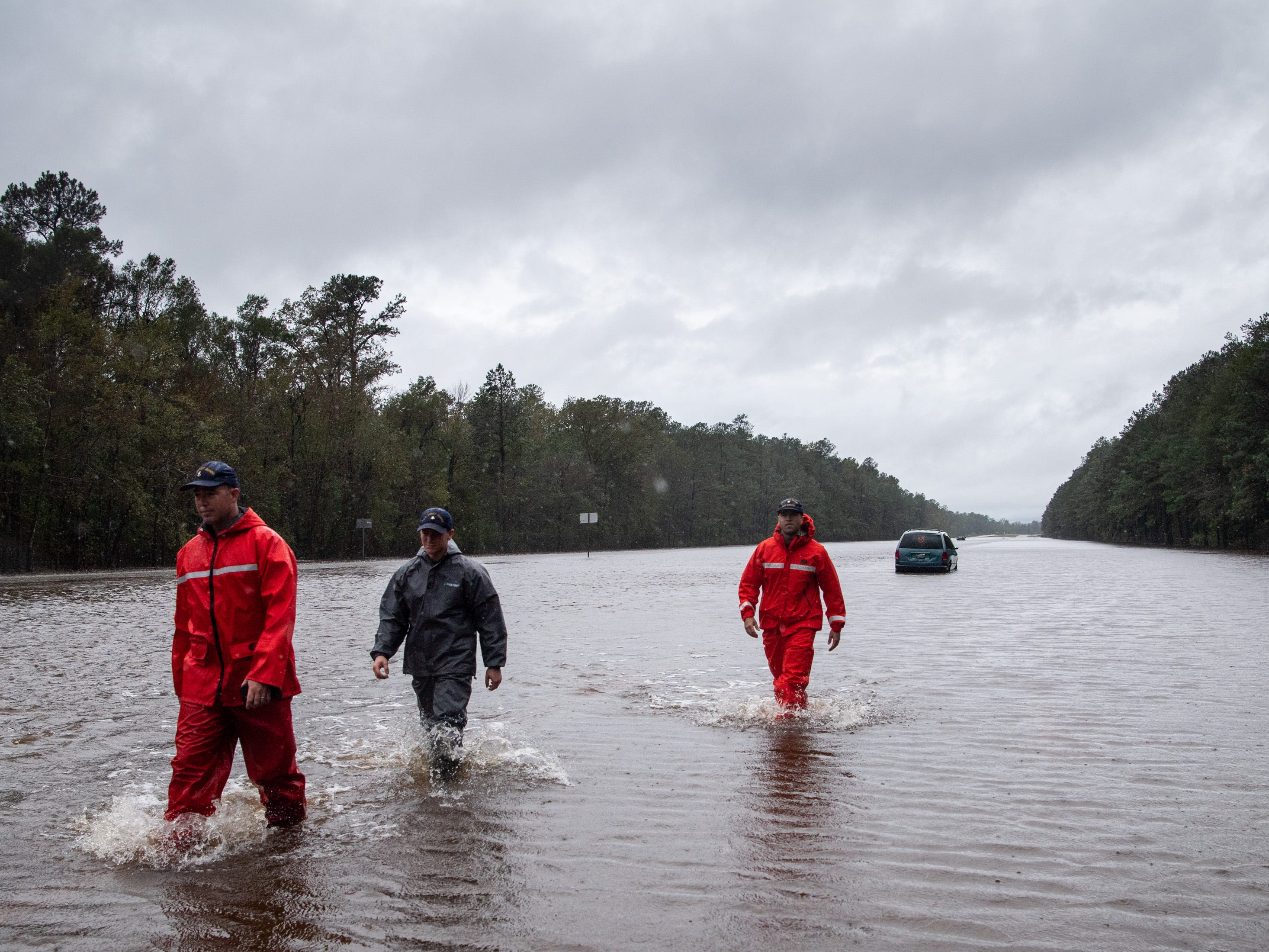 Coast Guardsmen check on abandoned cars on Andrew Jackson Highway near Hallsboro, N.C., Sunday, Sept. 16, 2018.