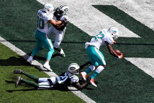 Miami Dolphins running back Kenyan Drake (32) scores a touchdown with pressure from New York Jets cornerback Morris Claiborne (21) in Week 2 at MetLife Stadium in East Rutherford, NJ on Sunday, September 16, 2018.
