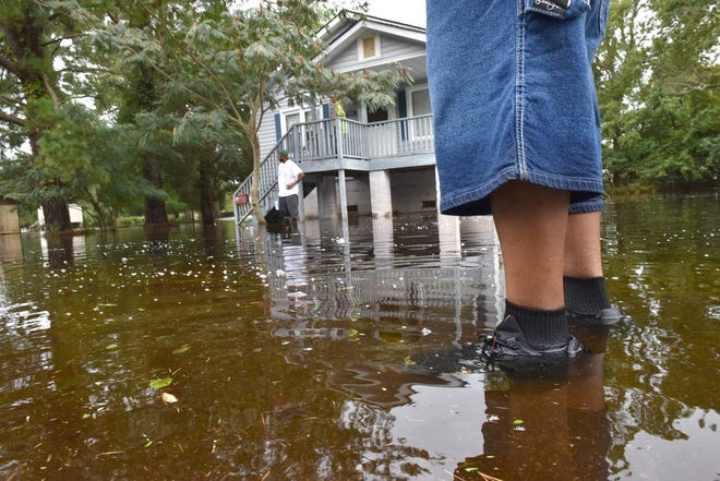 Sep 15, 2018; Belhaven, NC, USA; A man walks back to his home in high water on E. Pantego St in Belhaven, N.C. on Saturday afternoon on September 15, 2018. Hurricane Florence brought a lot of rain to the area flooding the streets and home. Mandatory Credit: Tariq Zehawi/NorthJersey.com via USA TODAY NETWORK