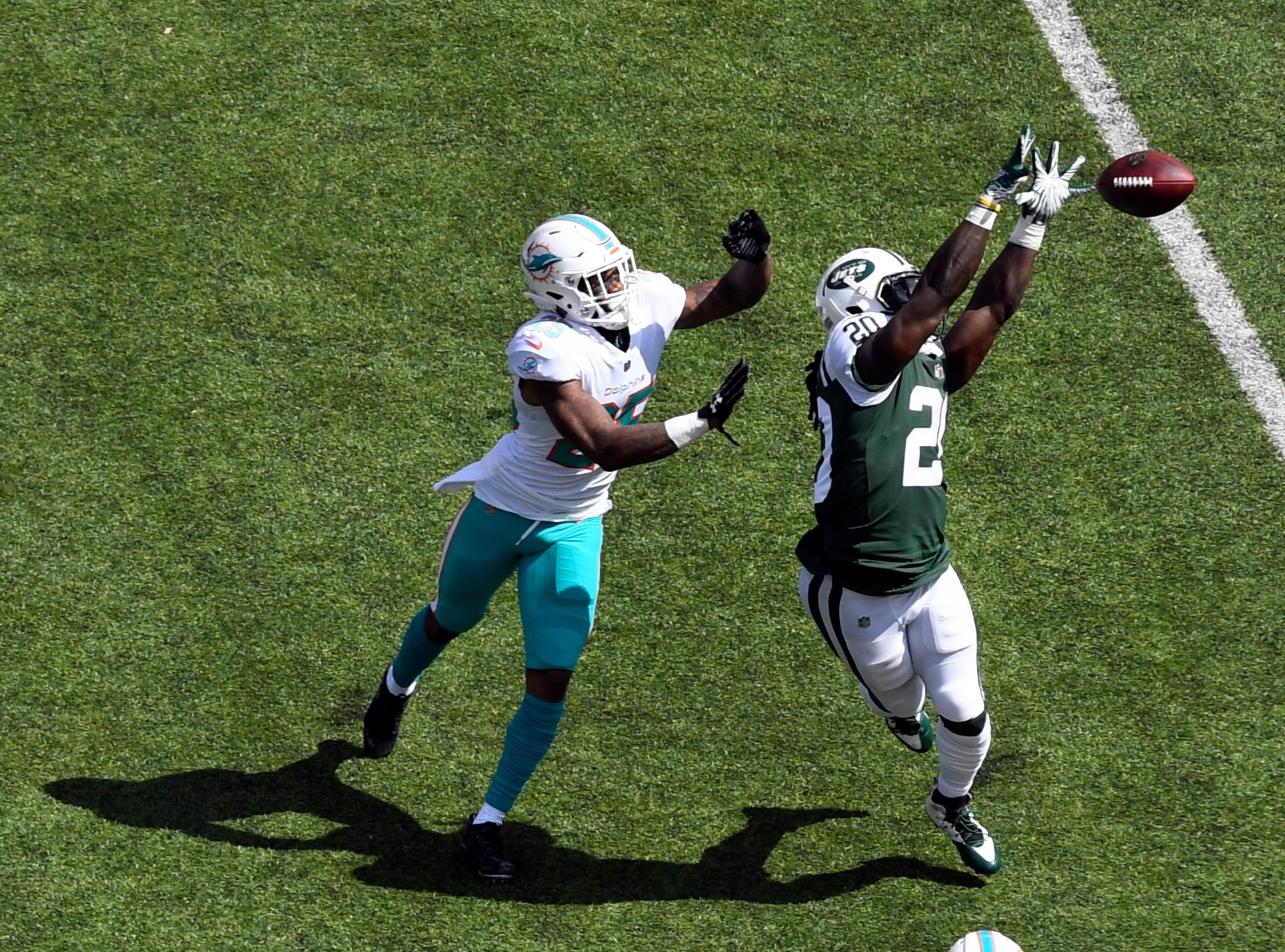 New York Jets running back Isaiah Crowell (20) reaches up for the ball but cannot complete a pass with pressure from Miami Dolphins cornerback Xavien Howard (25). The New York Jets lose to the Miami Dolphins 20-12 in Week 2 at MetLife Stadium in East Rutherford, NJ on Sunday, September 16, 2018.