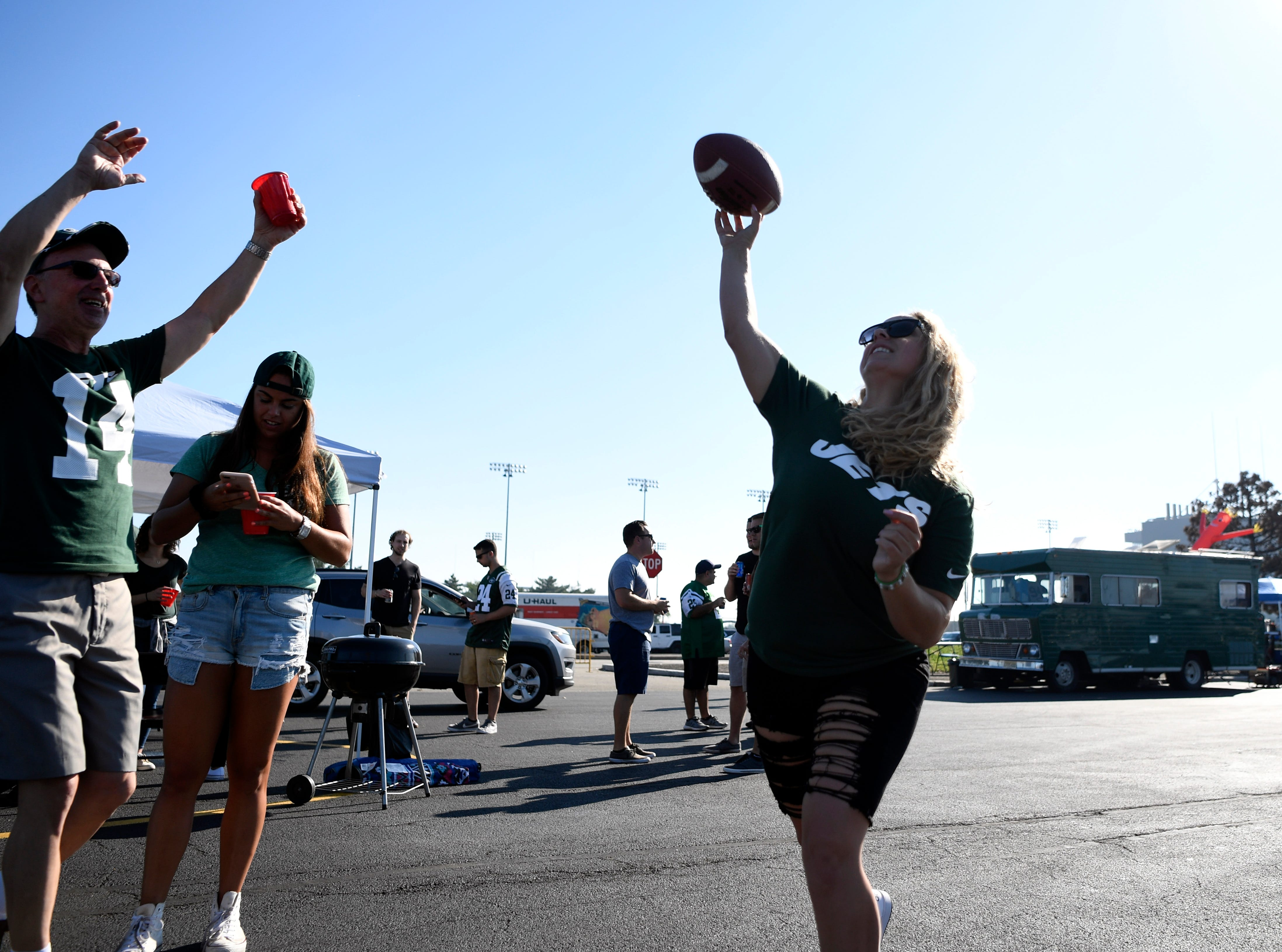 Paramus residents Ally Vergona, right, throws the football as Ed Boffalo pretends to block her. New York Jets face the Miami Dolphins in Week 2 at MetLife Stadium in East Rutherford, NJ on Sunday, September 16, 2018.