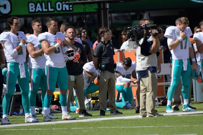 Miami Dolphins quarterback Ryan Tannehill (17) stands with teammates during the playing of the national anthem before an NFL football game Sunday, Sept. 16, 2018, in East Rutherford, N.J. (AP Photo/Bill Kostroun)