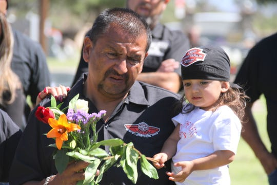 "Ramon Pena II and his daughter, Mia Harley, 2, placed flowers at the grave site of his son, Ramon ""MoMo"" Pena III. MoMo died in 2009 in a vehicle vs. horse accident on the outskirts of Deming."