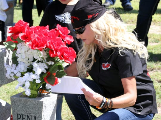 "Natasha Pena placed flowers and a sash at the grave site of her son Ramon ""Momo"" Pena III."