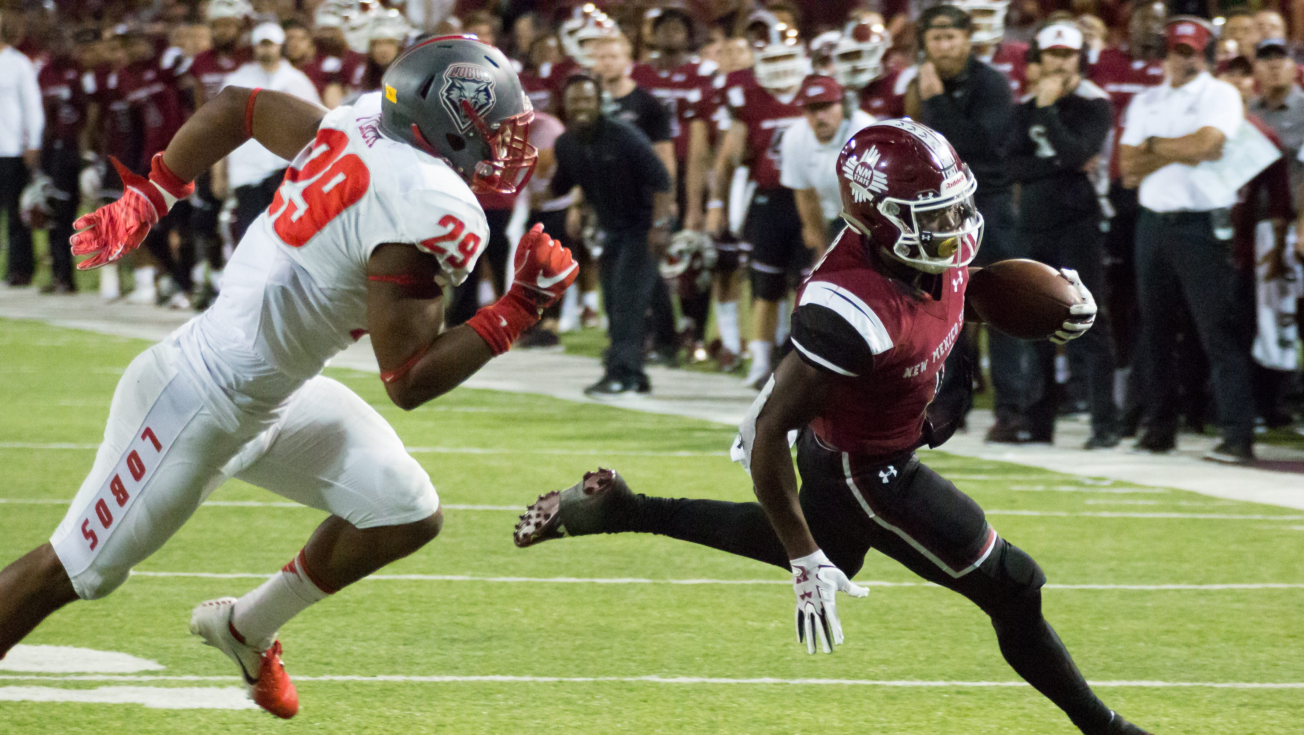 NMSU's Jason Huntley runs with the ball as UNM's Jalin Burrell looks to make the stop  on Saturday, September 15, 2018, at Aggie Memorial Stadium.