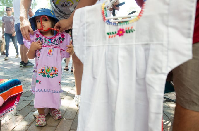 Amariz Leon -Garcia, 2, of Las Cruces, is fitted for a dress at the Abuelos Cuios booth  on Sunday, September 16, 2018 during the Diez y Seis de Septiembre Fiesta.