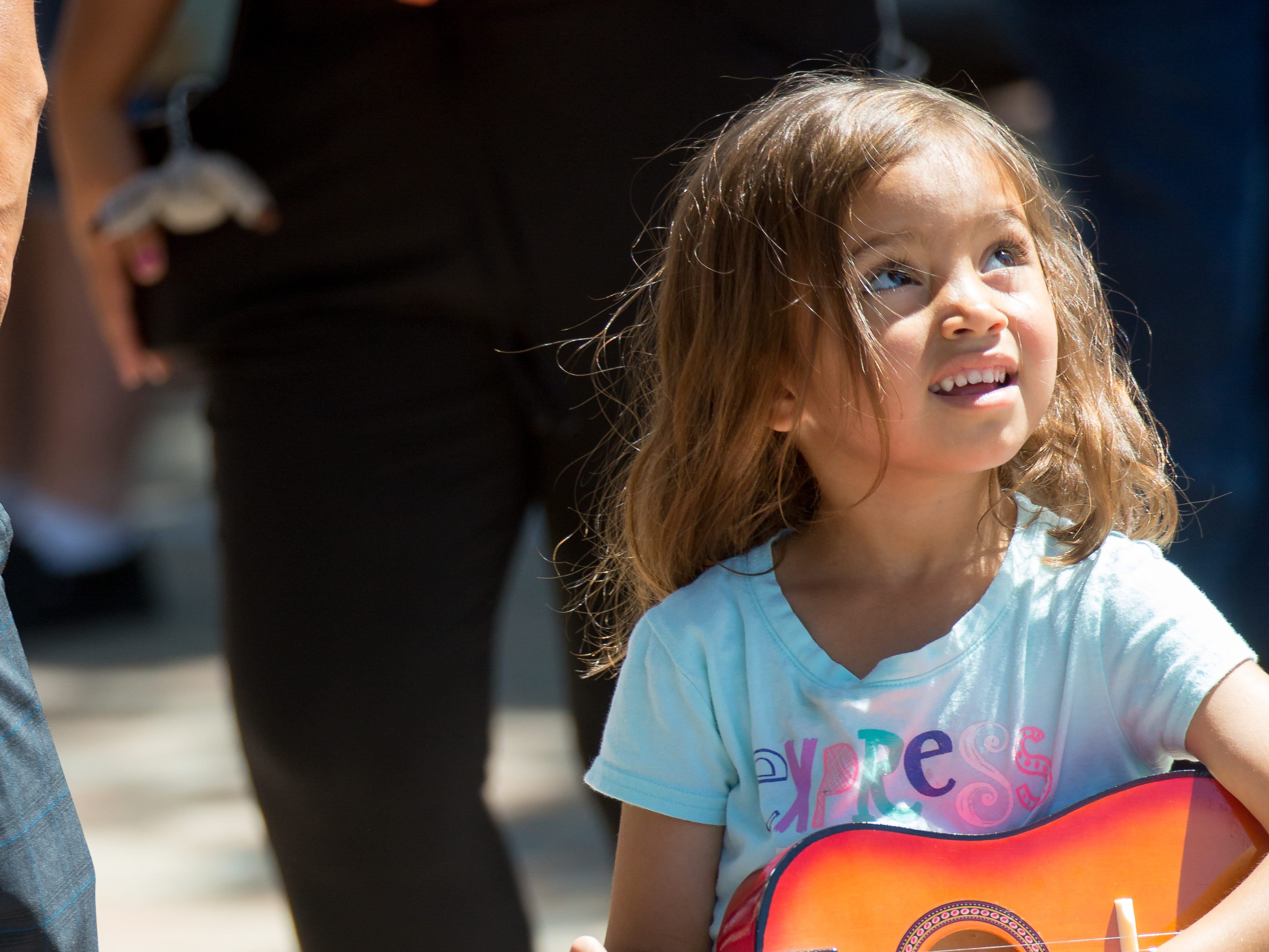 Natalie Mumez, 5, of Las Cruces, plays with her toy guitar on Sunday, September 16, 2018 during the Diez y Seis de Septiembre Fiesta at the Mesilla Plaza.