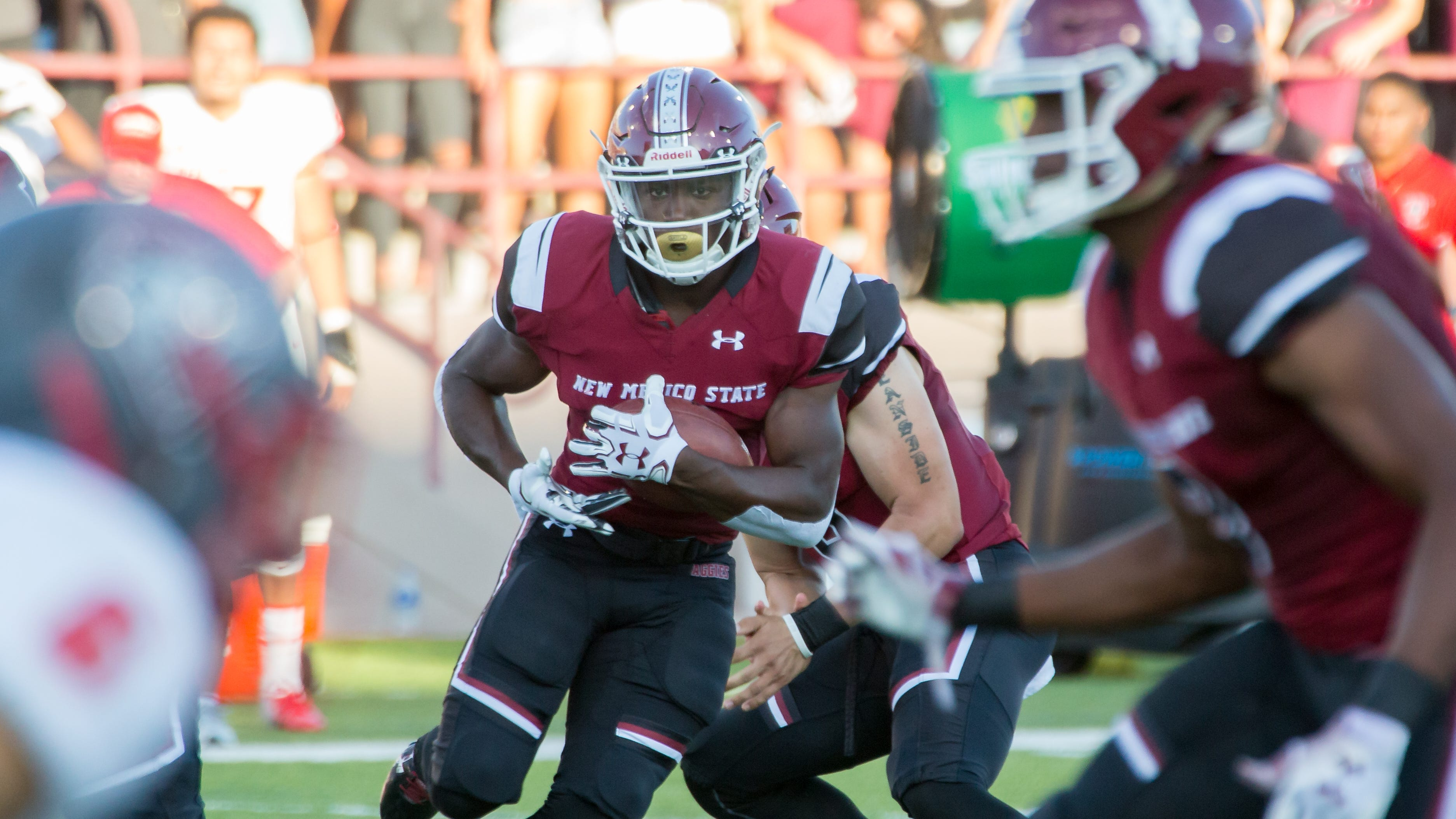 NMSU's Jason Huntley runs with the ball as UNM defender looks to make the stop on Saturday, September 15, 2018, at Aggie Memorial Stadium.