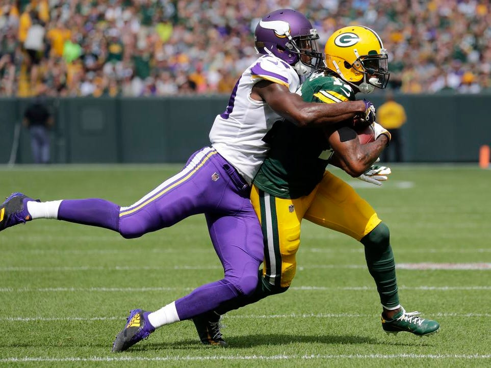 Green Bay Packers wide receiver Davante Adams (17) is tackled by Minnesota Vikings defensive back Xavier Rhodes (29) in the first half during their football game Sunday, Sept. 16, 2018, at Lambeau Field in Green Bay, Wis.