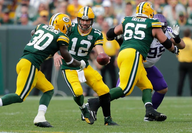 Green Bay Packers quarterback Aaron Rodgers (12) hands off to running back Jamaal Williams (30) in the third quarter against the Minnesota Vikings during their football game Sunday, Sept. 16, 2018, at Lambeau Field in Green Bay, Wis.