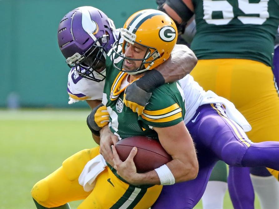 Green Bay Packers quarterback Aaron Rodgers (12) is sacked by defensive tackle Sheldon Richardson (93) against the Minnesota Vikings Sunday, September 16, 2018 at Lambeau Field in Green Bay, WIs.