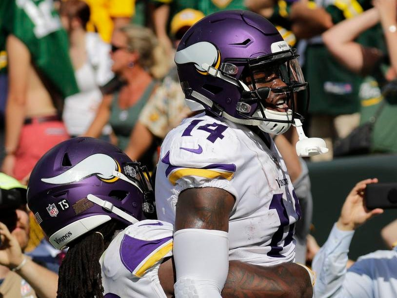 Minnesota Vikings wide receiver Stefon Diggs (14) celebrates scoring a two-point conversion to tie the game late in the fourth quarter with running back Dalvin Cook (33) against the Green Bay Packers during their football game Sunday, Sept. 16, 2018, at Lambeau Field in Green Bay, Wis.