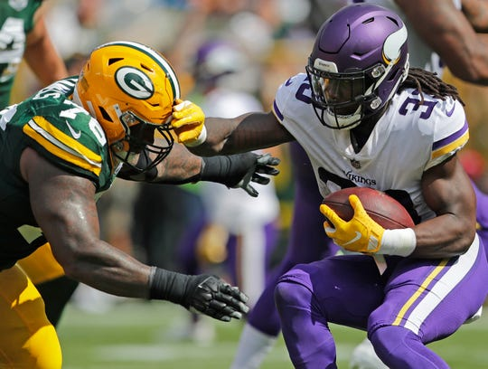 Green Bay Packers defensive tackle Mike Daniels (76) tackles Minnesota Vikings running back Dalvin Cook (33) in the second quarter at Lambeau Field on Sunday, September 16, 2018 in Green Bay, Wis.