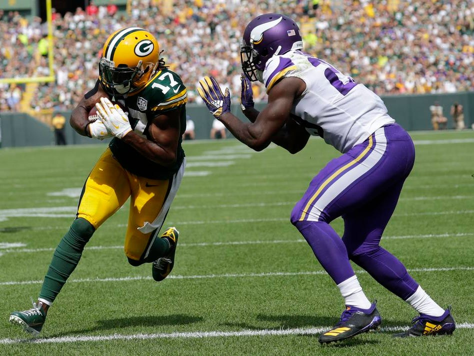 Green Bay Packers wide receiver Davante Adams (17) scores a touchdown in the second quarter against Minnesota Vikings defensive back Xavier Rhodes (29) during their football game Sunday, Sept. 16, 2018, at Lambeau Field in Green Bay, Wis.
