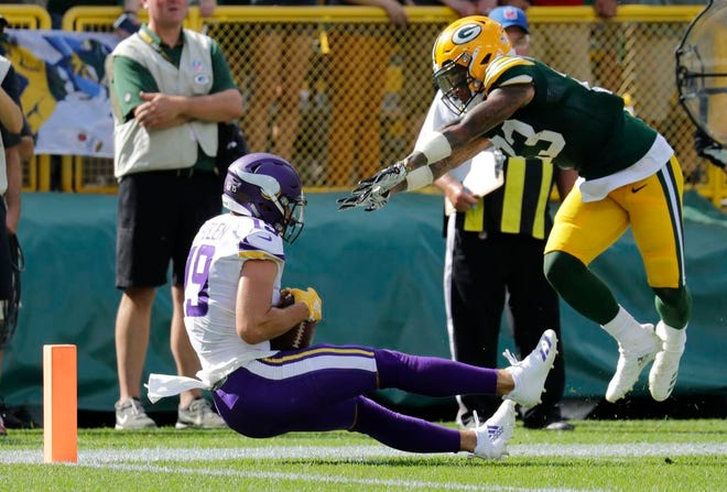 Minnesota Vikings wide receiver Adam Thielen (19) scores a touchdown against Green Bay Packers cornerback Jaire Alexander (23) late in the fourth quarter during their football game Sunday, Sept. 16, 2018, at Lambeau Field in Green Bay, Wis. The Vikings scored a two point conversion to tie the game.