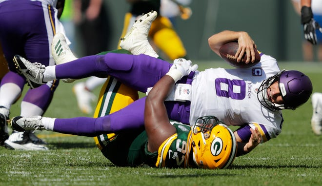 Green Bay Packers nose tackle Kenny Clark (97) sacks Minnesota Vikings quarterback Kirk Cousins (8) in the third quarter during their football game Sunday, Sept. 16, 2018, at Lambeau Field in Green Bay, Wis.