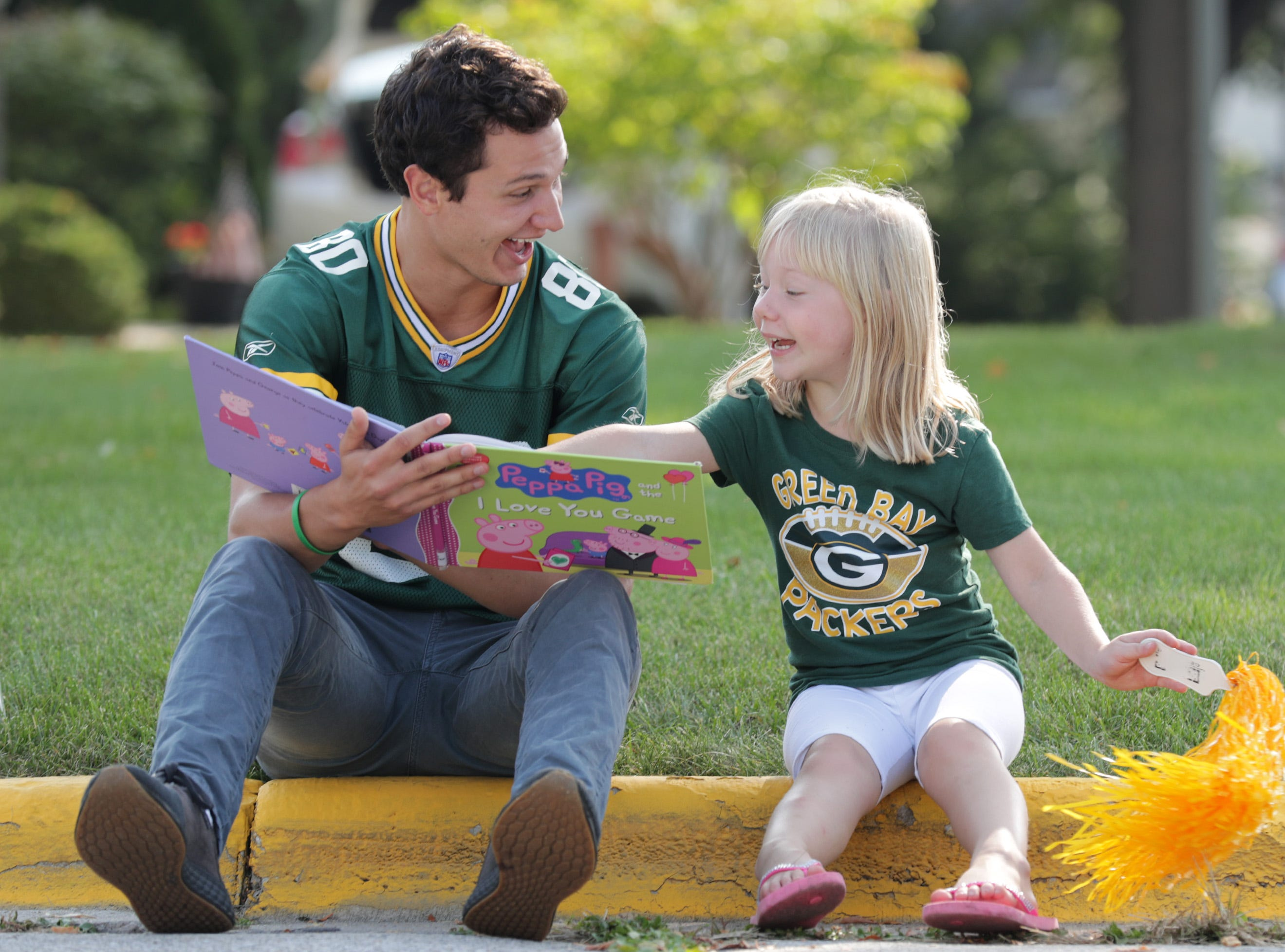 Neighbors Jake Imig and Lily Sota read a book together while helping to park cars on Wildwood Ln. before the Green Bay Packers host the Minnesota Vikings on Sunday, September 16, 2018, at Lambeau Field in Green Bay, Wis.
