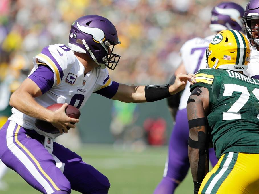 Minnesota Vikings quarterback Kirk Cousins (8) spins away from Green Bay Packers defensive tackle Mike Daniels (76) in the third quarter at Lambeau Field on Sunday, September 16, 2018 in Green Bay, Wis.
