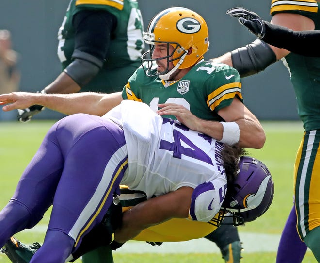 Green Bay Packers quarterback Aaron Rodgers (12) gets roughed by linebacker Eric Kendricks (54) in the 2nd quarter against the Minnesota Vikings Sunday, September 16, 2018 at Lambeau Field in Green Bay, WIs.