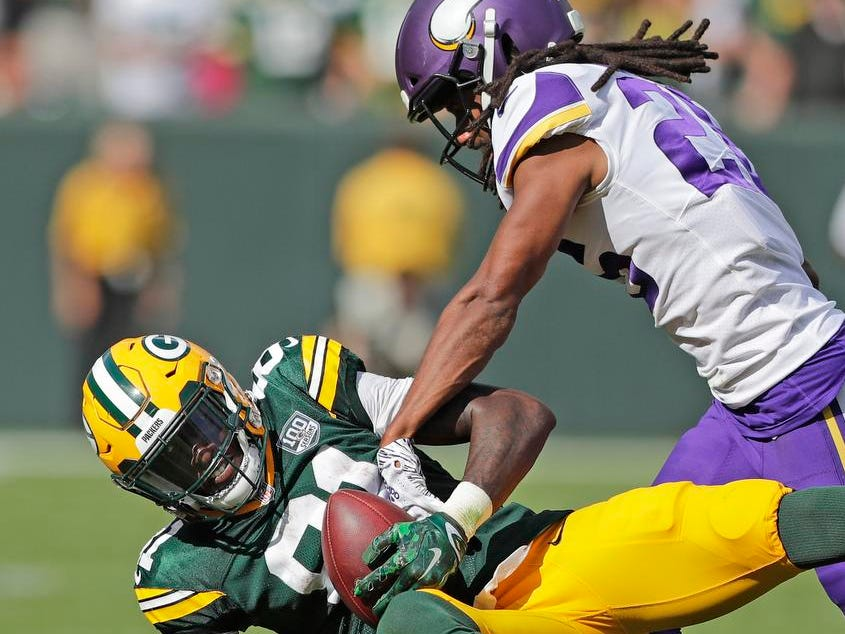 Green Bay Packers wide receiver Geronimo Allison (81) is hit by Minnesota Vikings cornerback Trae Waynes (26) after a catch in the fourth quarter at Lambeau Field on Sunday, September 16, 2018 in Green Bay, Wis.