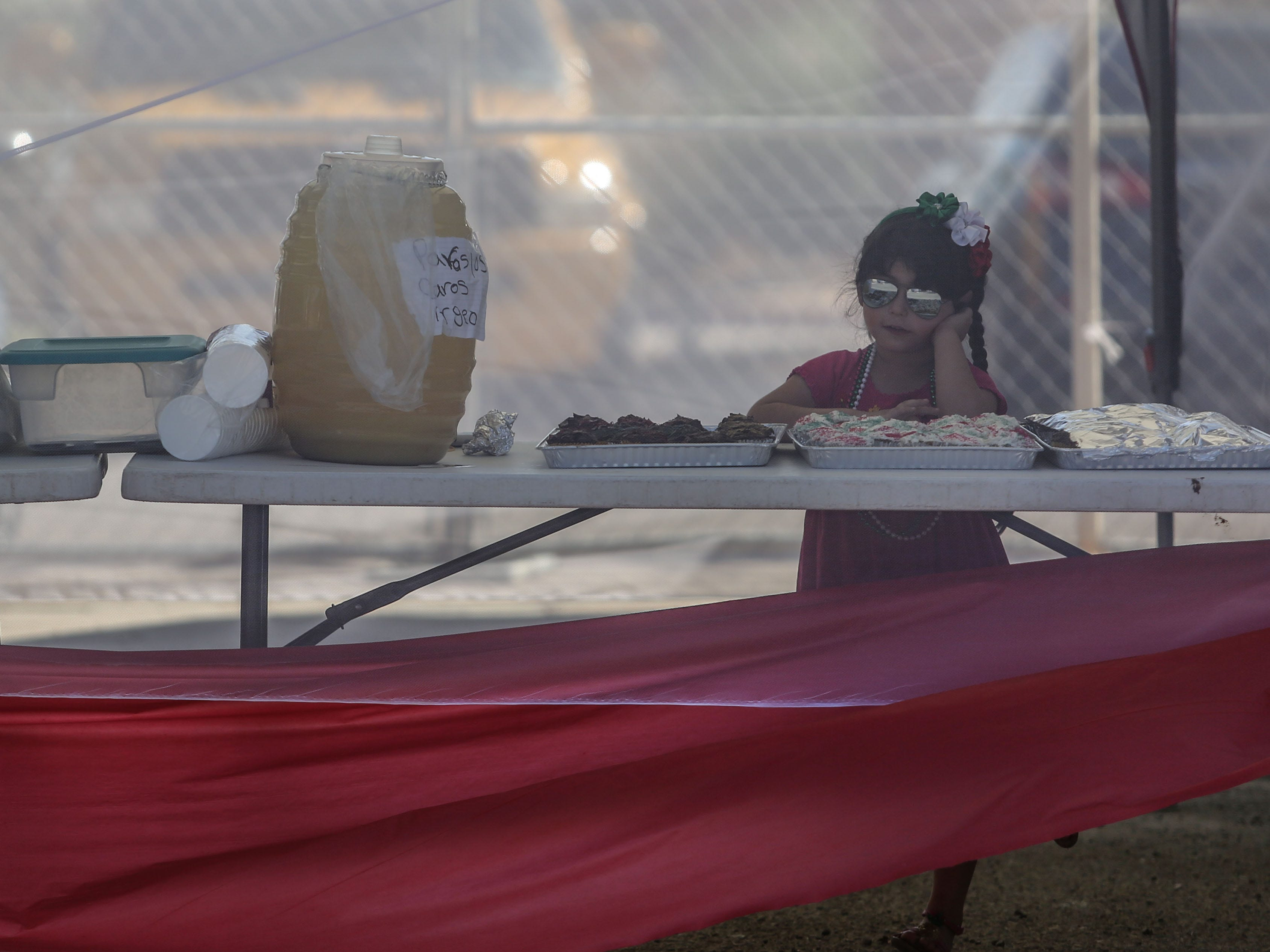 A girl keeps watch at the drinks booth at the Mexican independence day celebration at Our Virgin of Guadalupe Church in Mecca on Saturday, September 15, 2018.