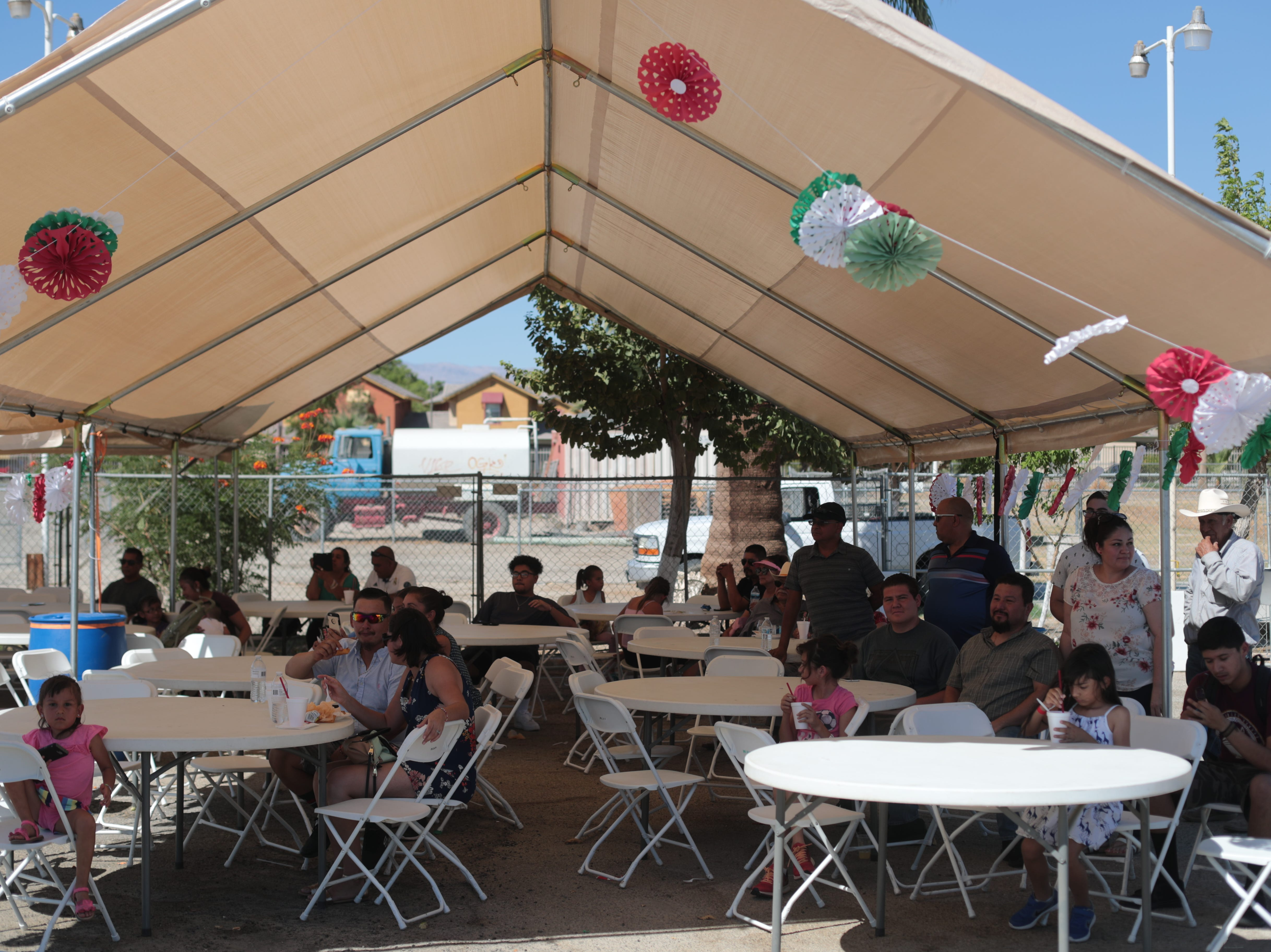 People in the shade at the Mexican independence day celebration at Our Virgin of Guadalupe Church in Mecca on Saturday, September 15, 2018.